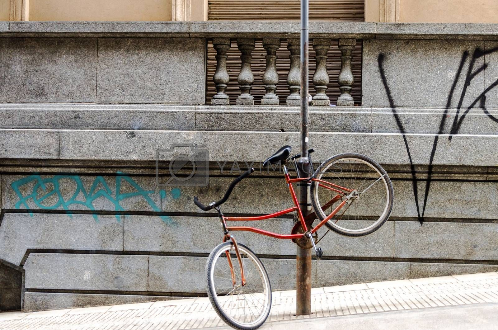 Red bicycle chained to a post in an urban setting