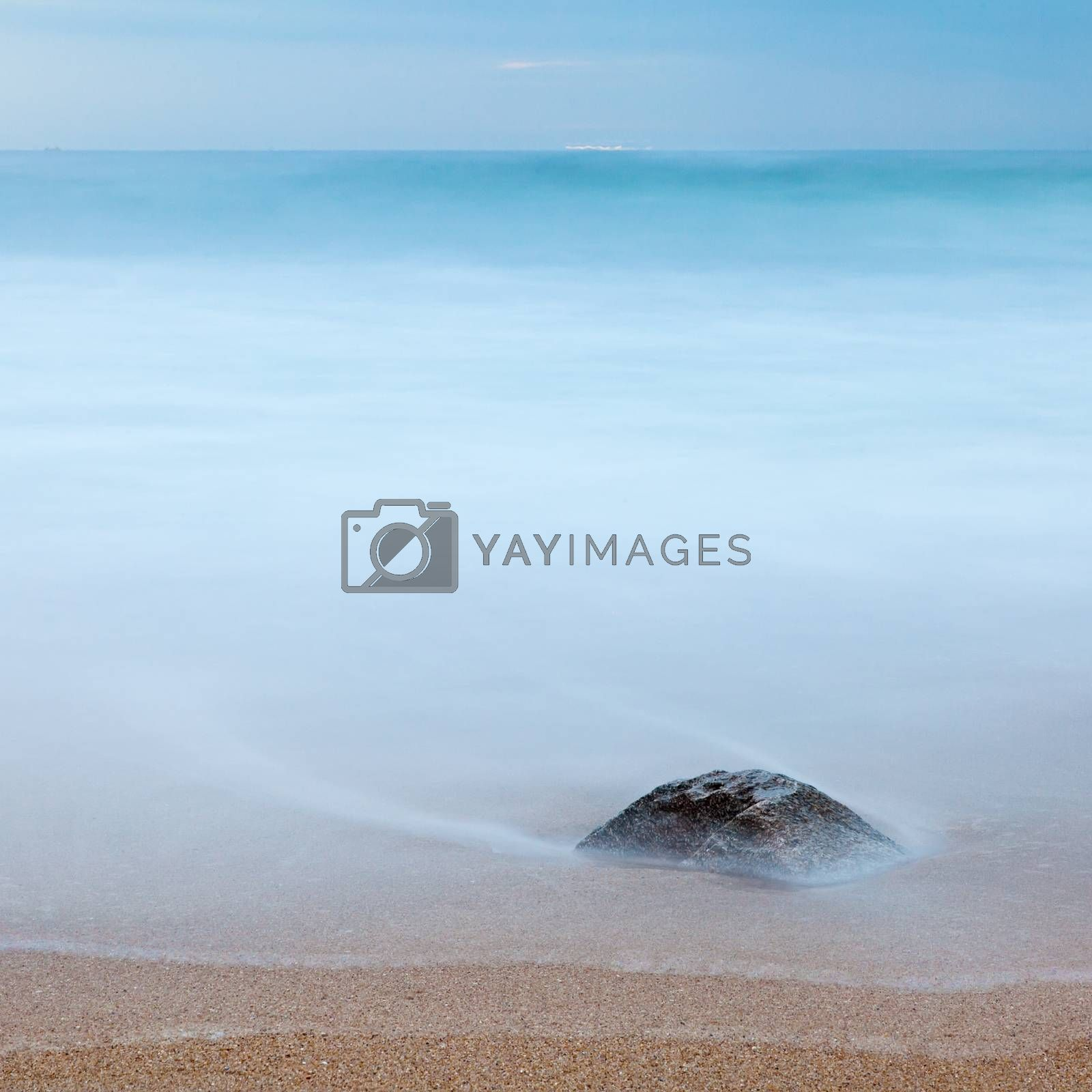 Photo of a rock on a beach, buried in the sand and covered by the ocean. Long exposure. Copy space.