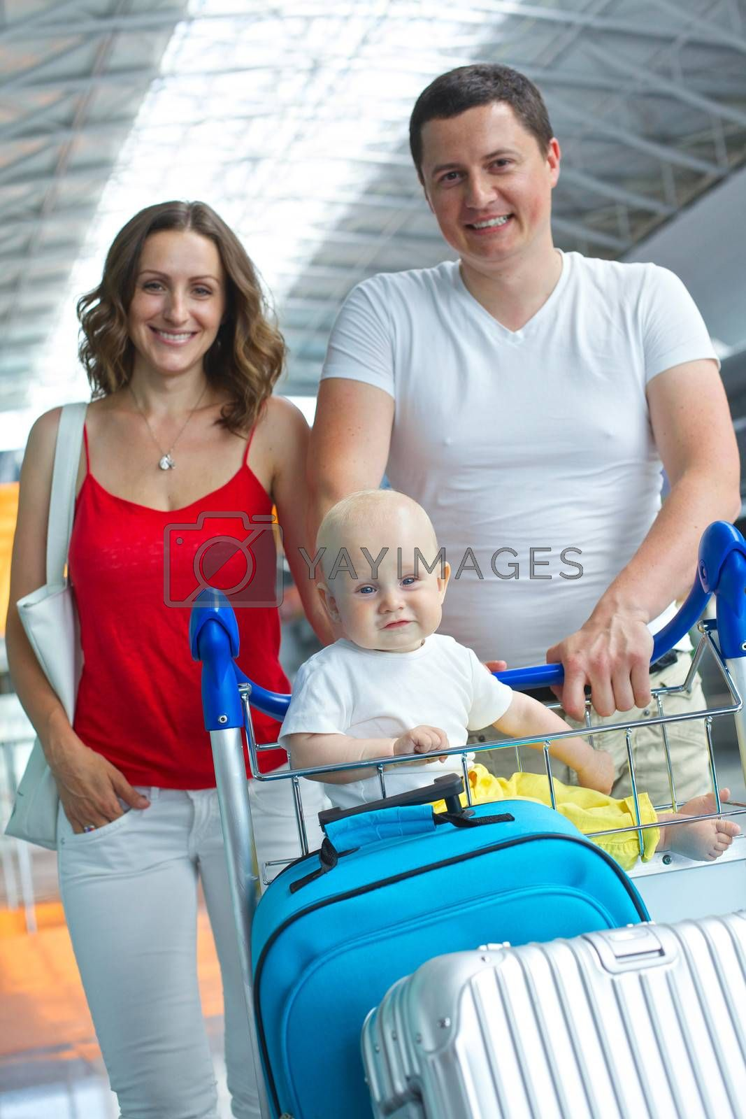 Standing traveling family with suitcases in airport