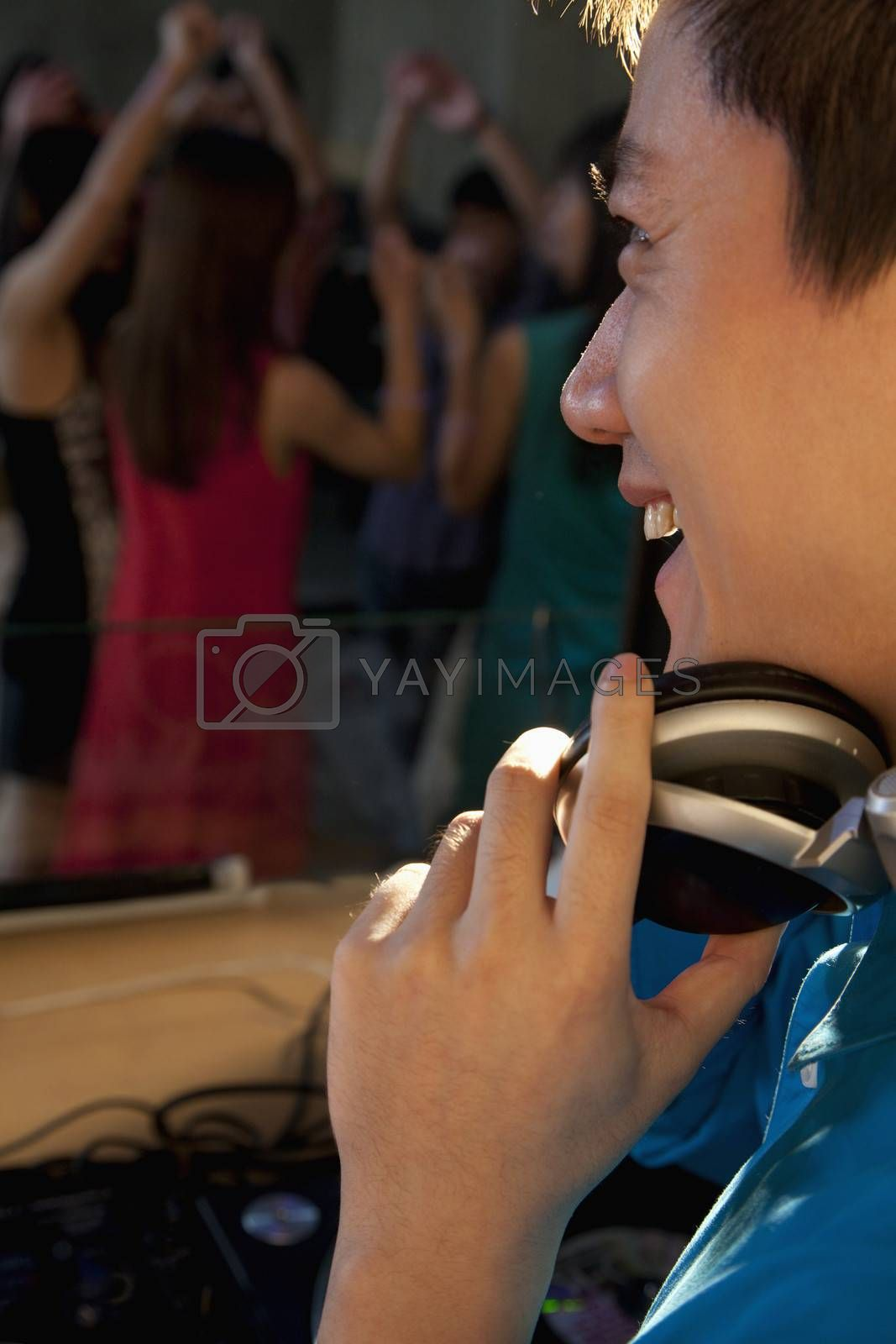 DJ laughing and watching the dancing crowd in nightclub