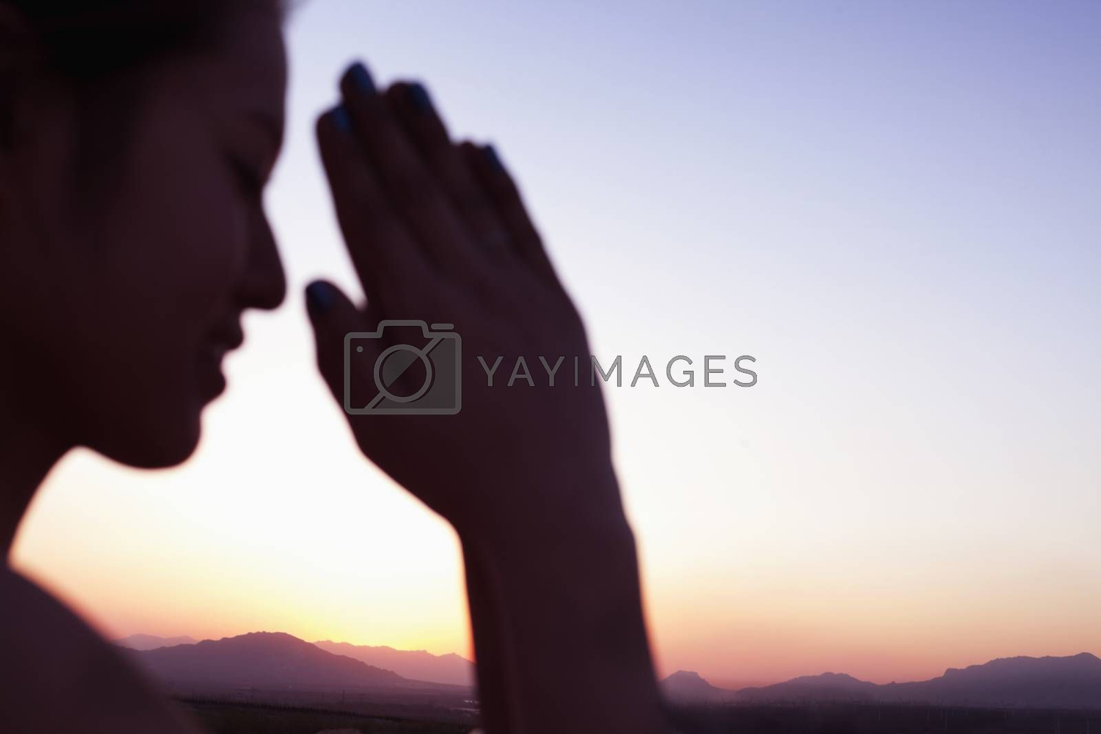 Serene young woman with eyes closed and hands together in prayer pose in the desert in China, focus on background