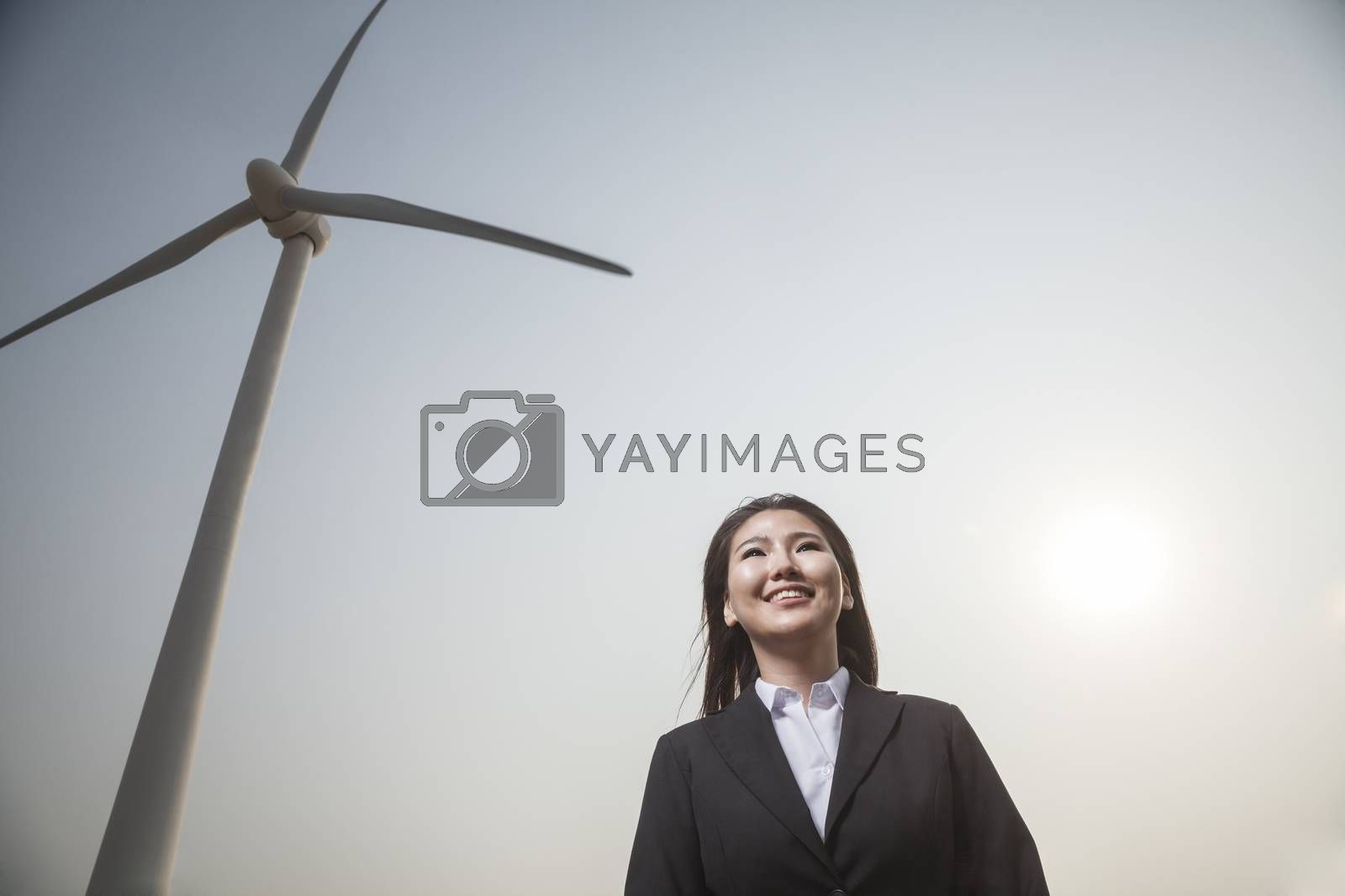 Portrait of smiling young businesswoman standing by a wind turbine