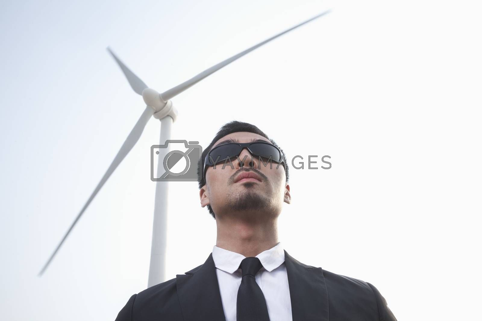 Portrait of serious young businessman in sunglasses standing by a wind turbine