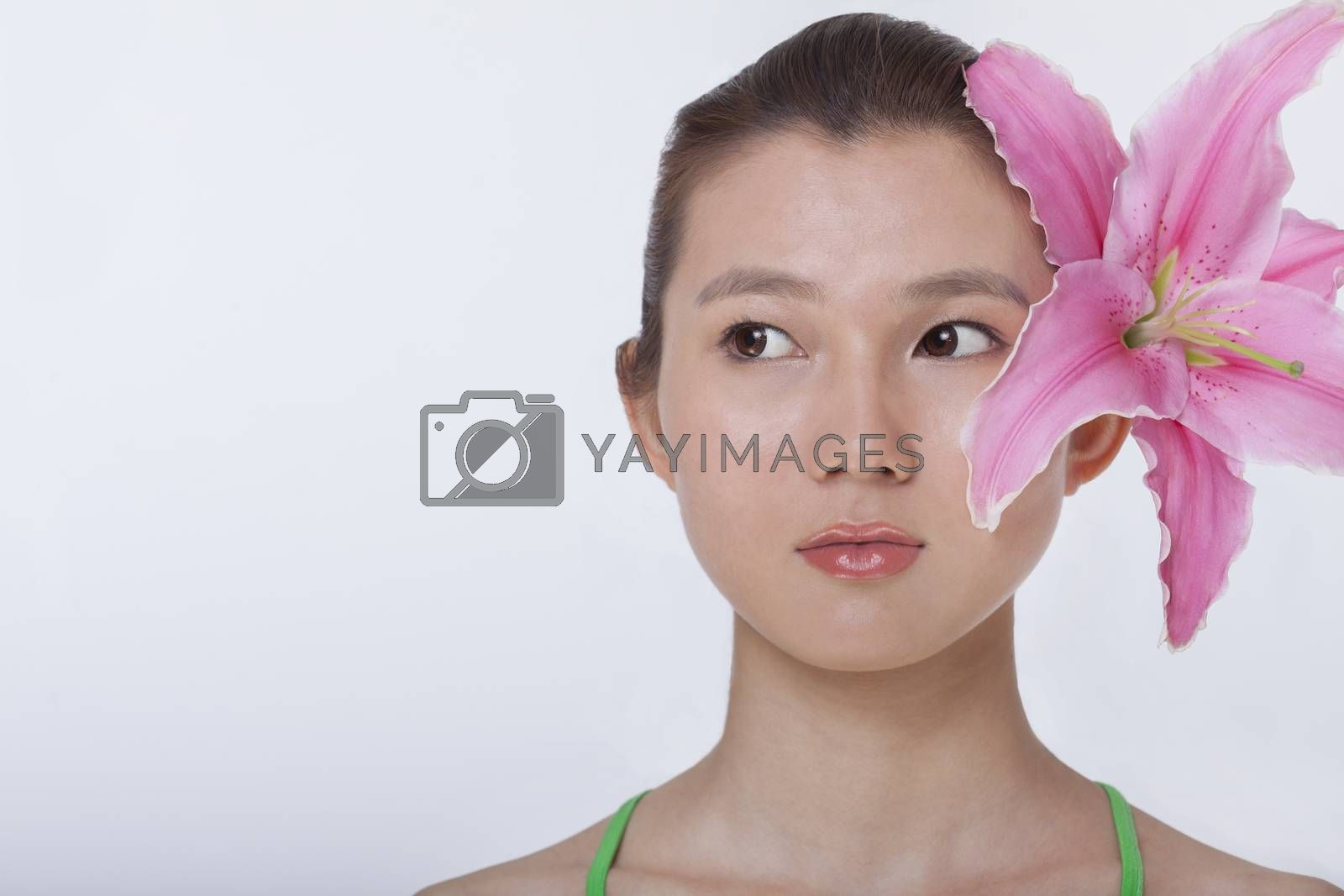 Portrait of young beautiful woman with a large pink flower tucked behind her ear, studio shot