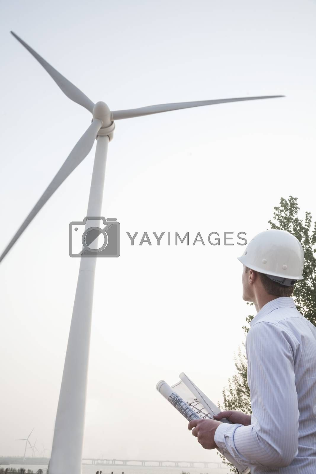 Young male engineer in a hardhat looking up at a wind turbine, blueprint in hand