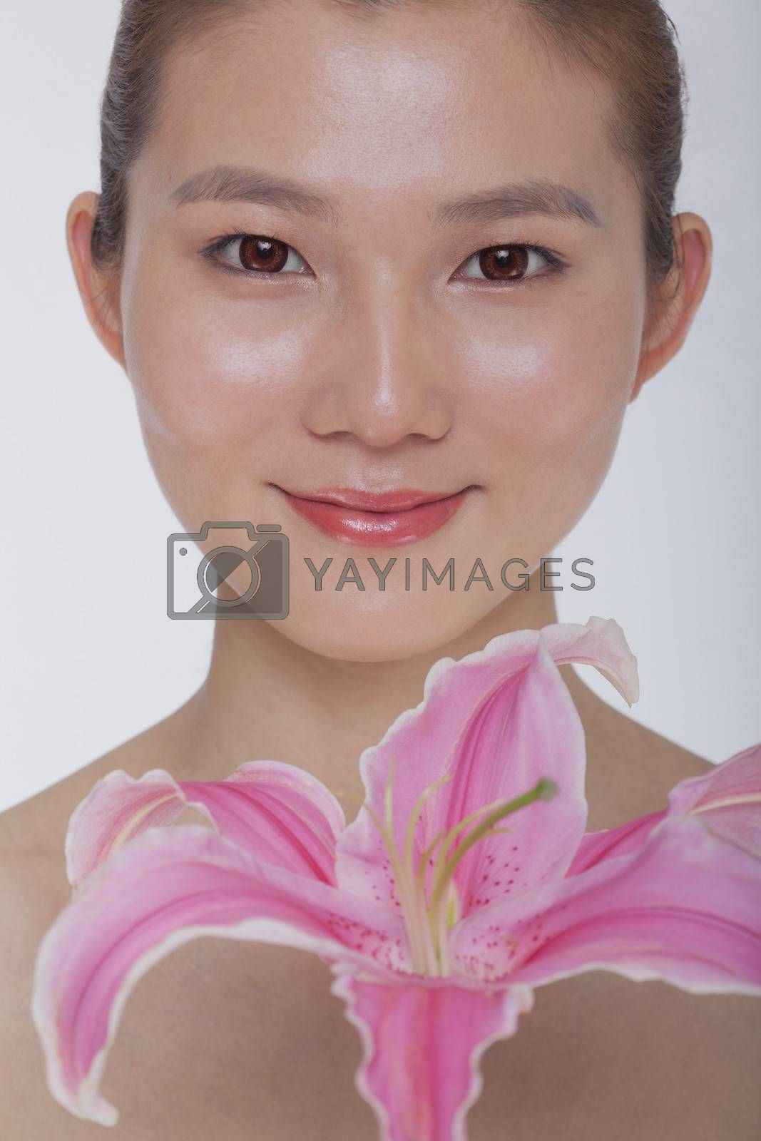 Portrait of young tranquil woman looking at camera with a large pink flower, studio shot