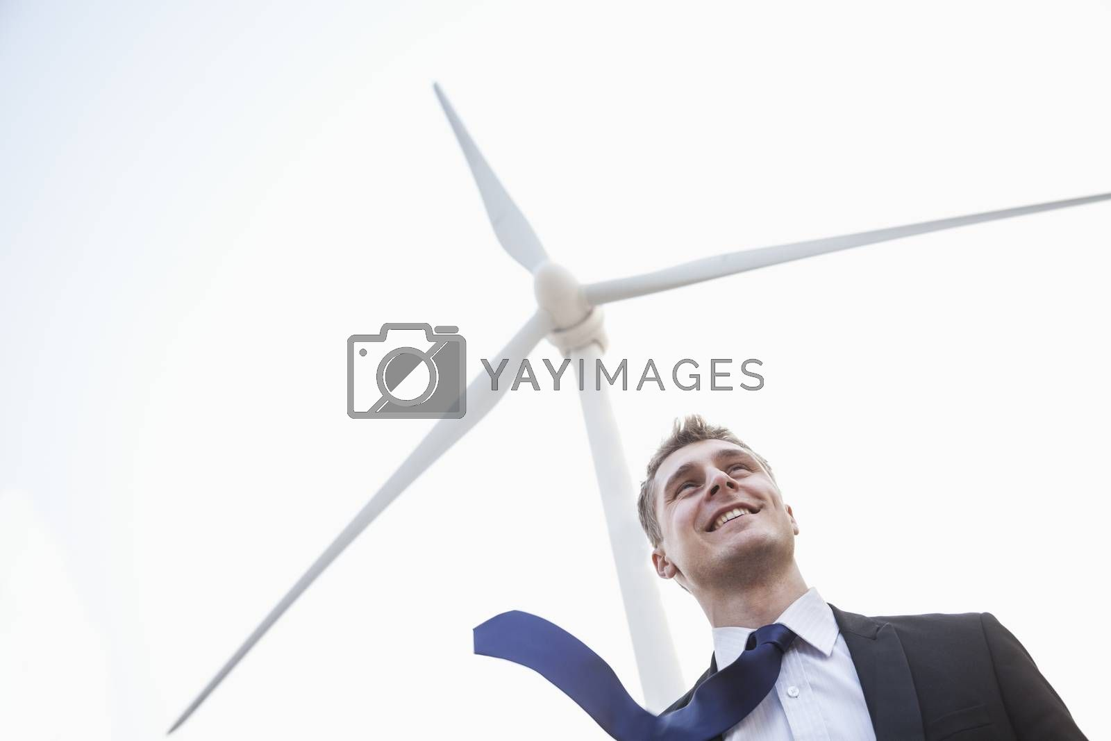 Young smiling businessman standing beside a wind turbine, tie is blowing in the wind