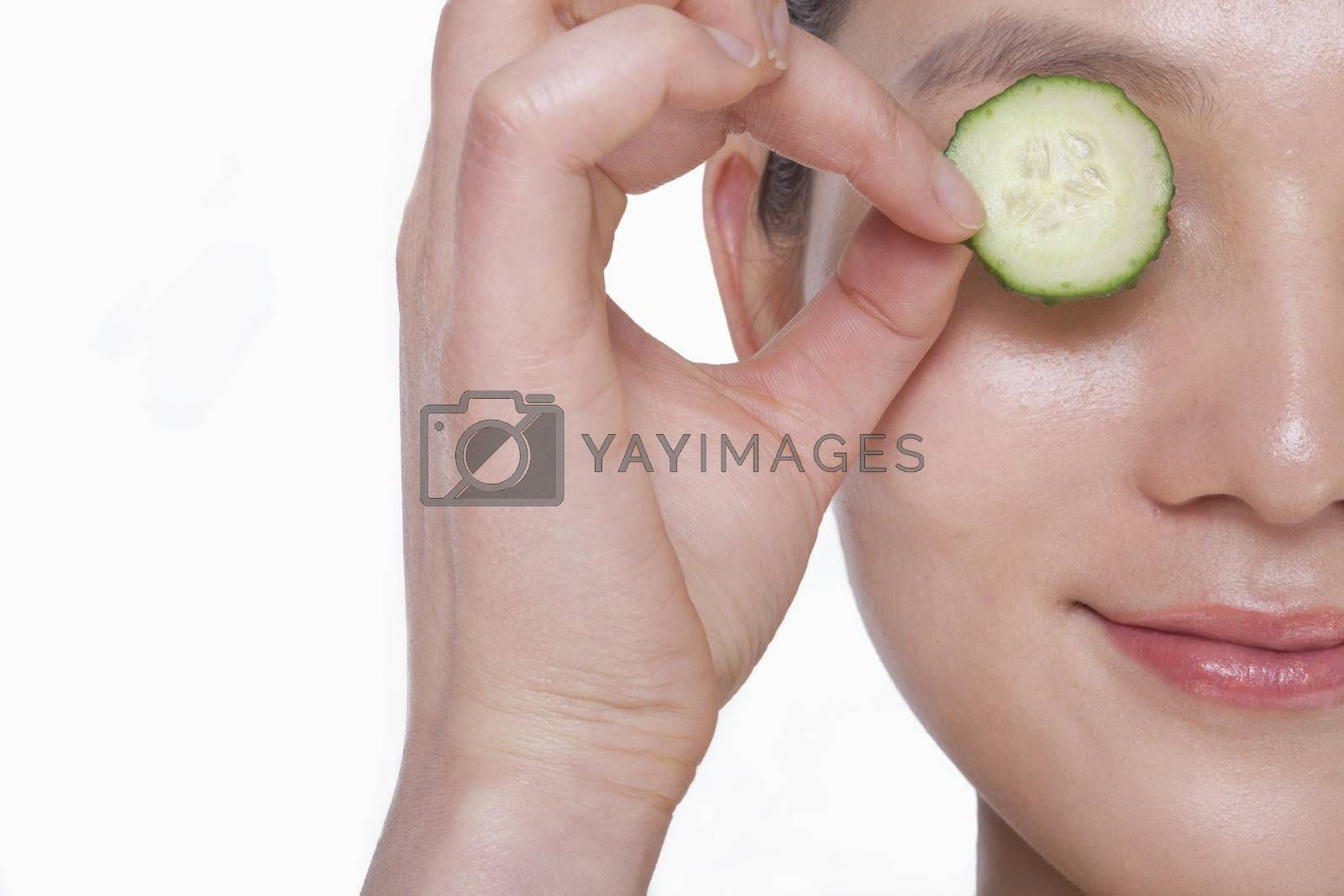 Close up of smiling young woman holding up a cucumber slice over her eye, studio shot