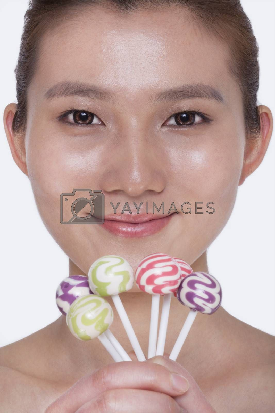Smiling young woman looking into camera and holding up colorful lollipops, studio shot