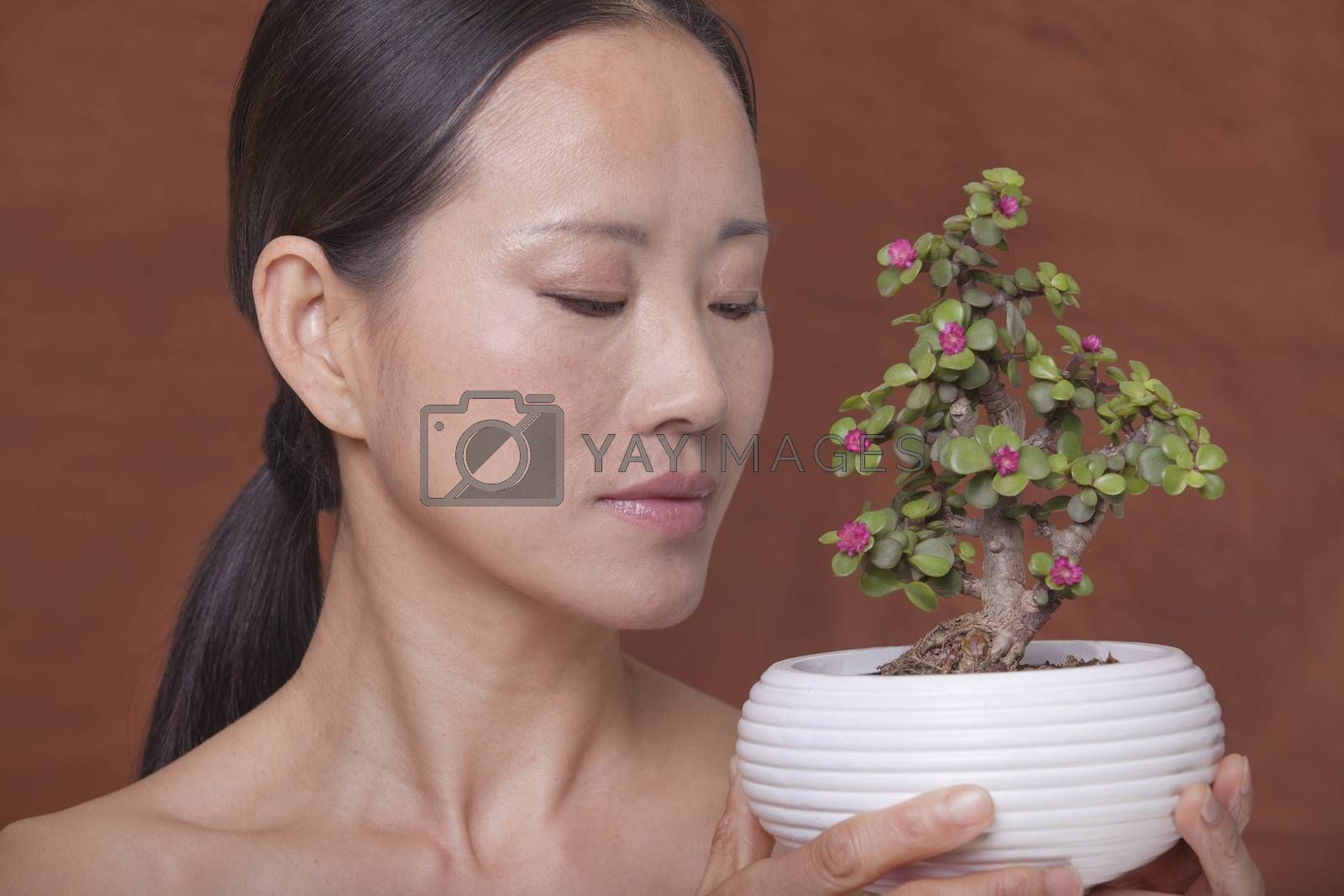 Shirtless woman holding and looking down at a small plant in a flower pot, studio shot