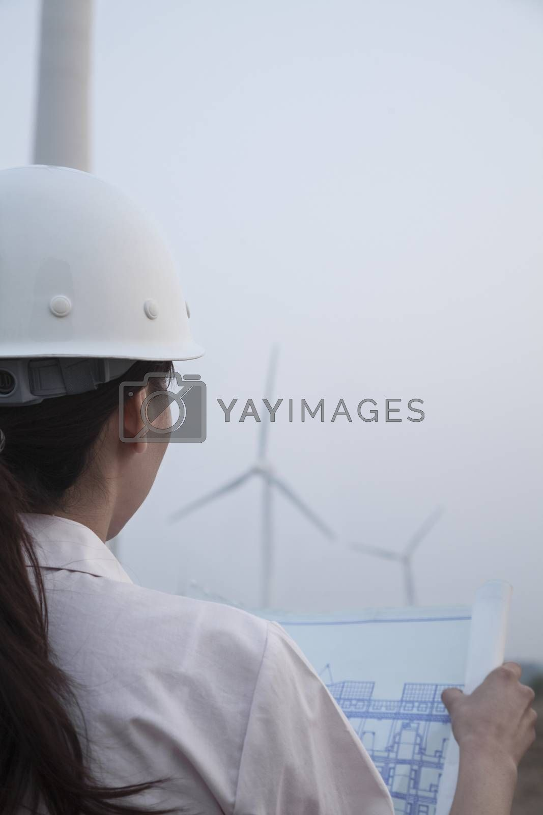 Young female engineer looking at blueprint with wind turbines in front of her, over the shoulder view