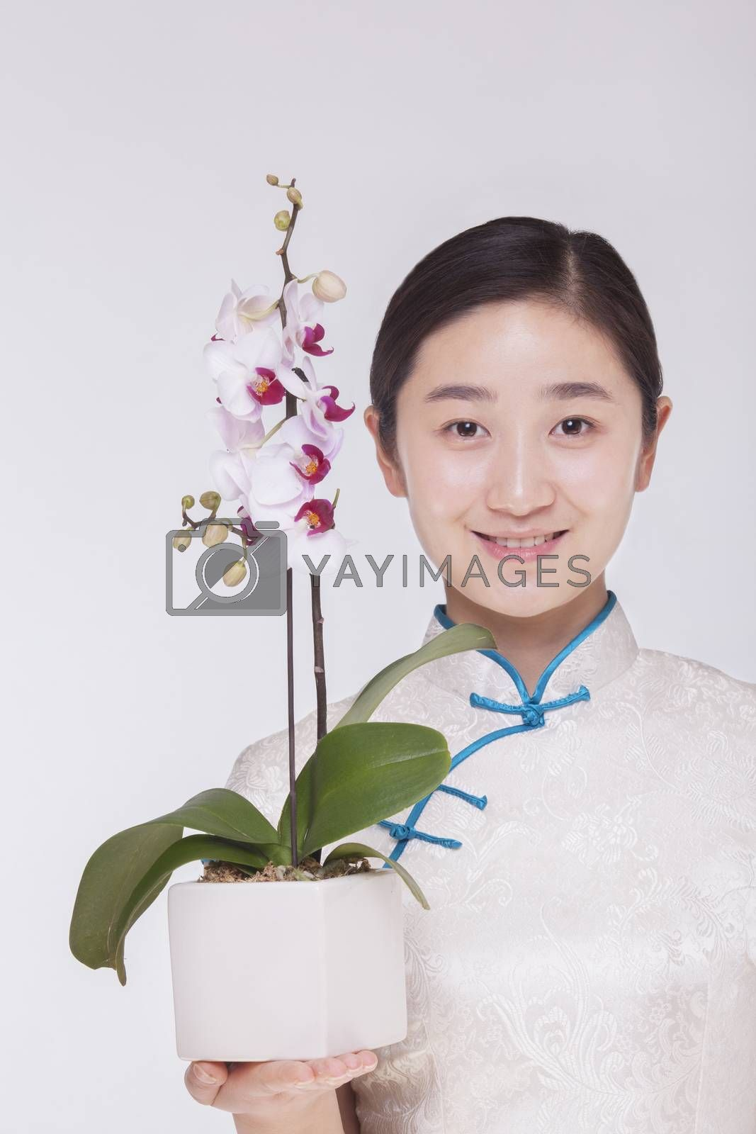 Portrait of smiling young woman holding a beautiful white flower in a flower pot, studio shot
