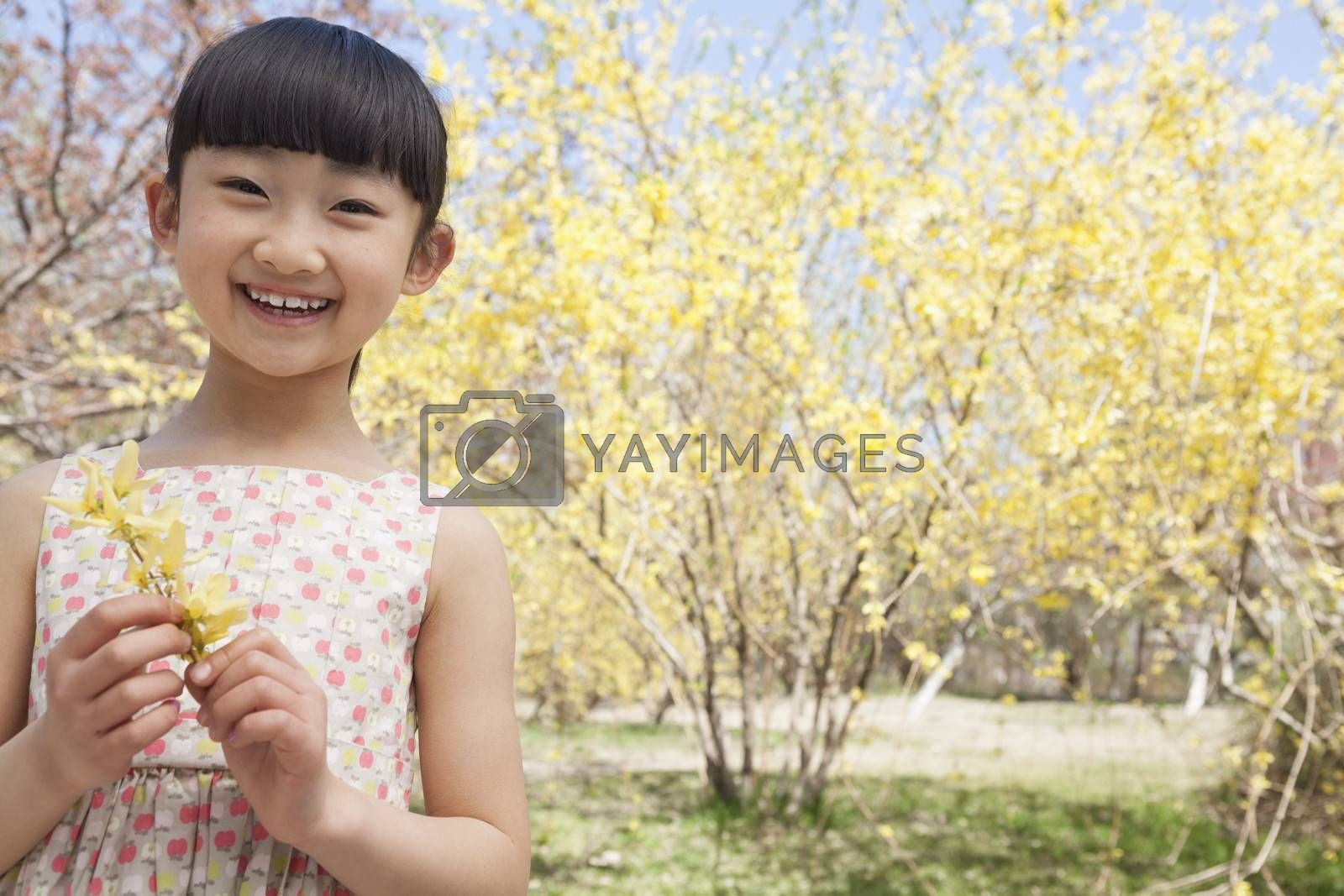 Portrait of smiling girl holding a yellow flower in the park in springtime