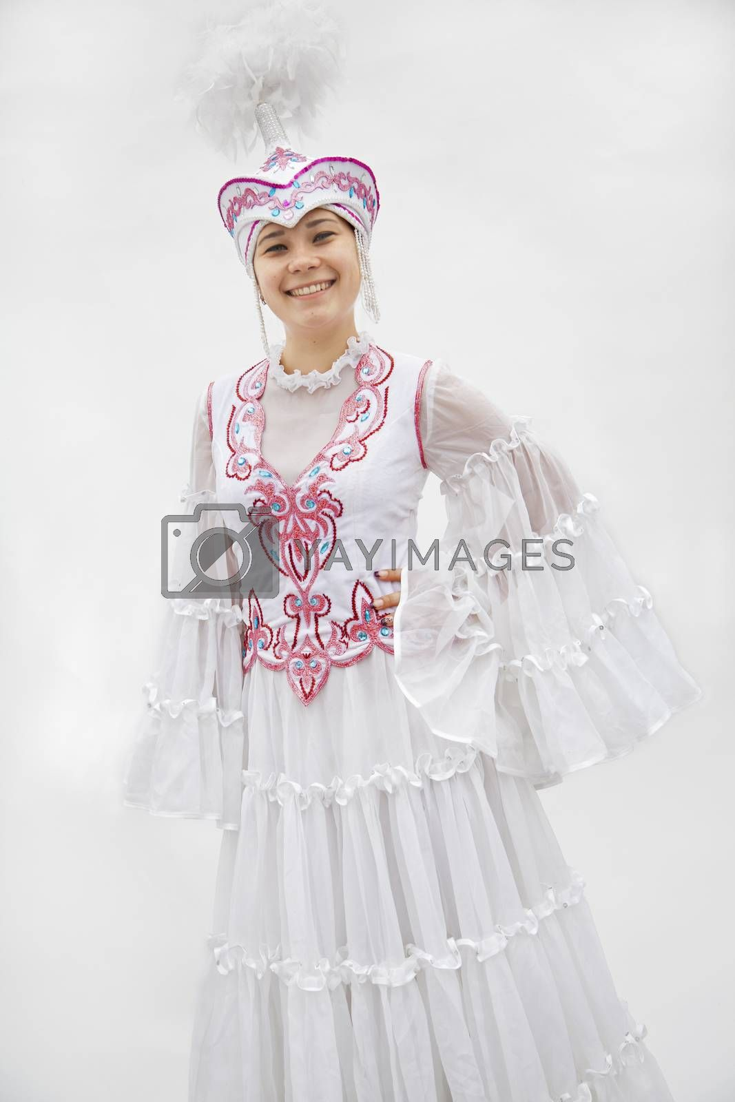 Portrait of young smiling woman in traditional clothing from Kazakhstan, studio shot