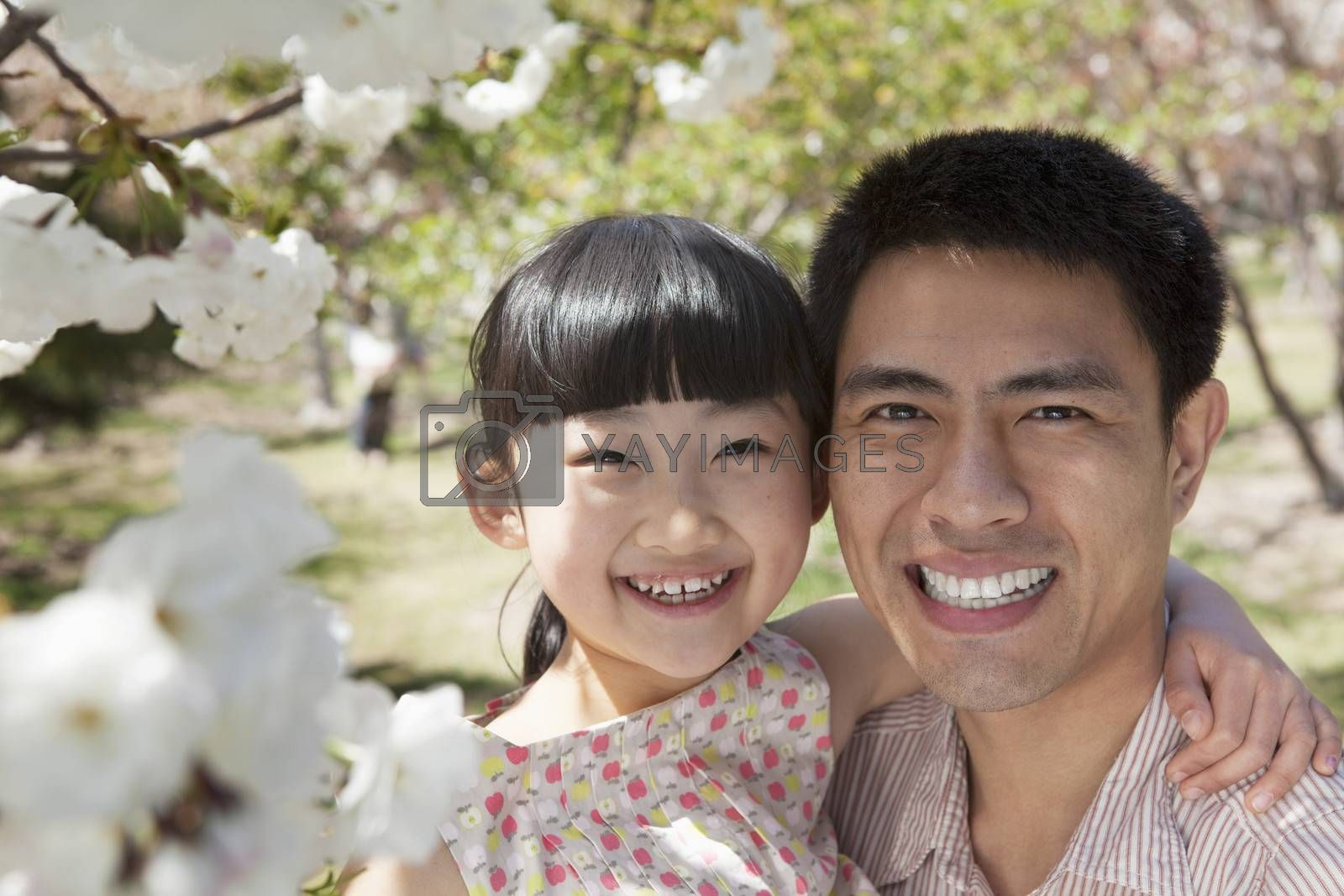 Smiling father and daughter enjoying the cherry blossoms on the tree in the park in springtime, portrait
