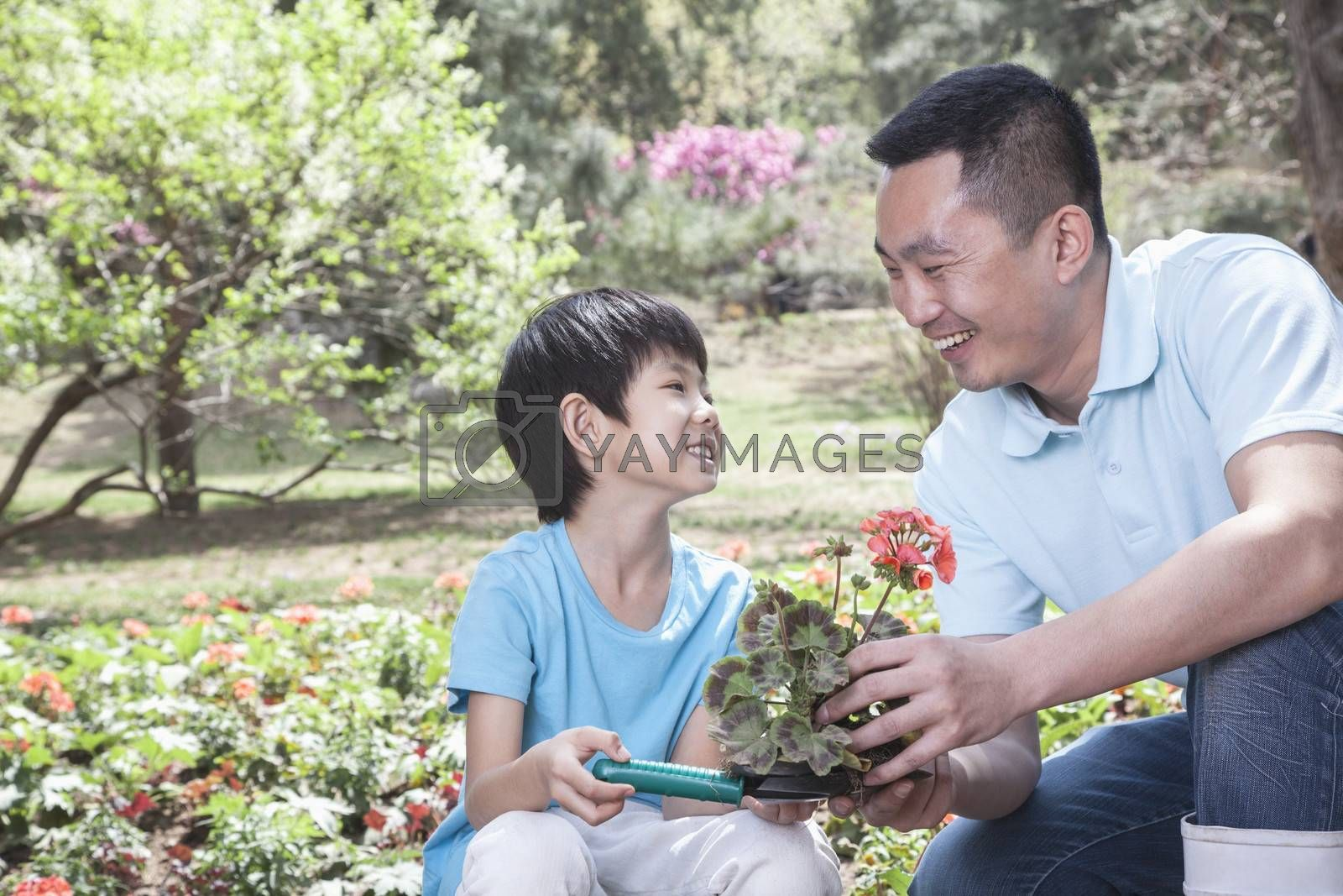 Father and son planting flowers.