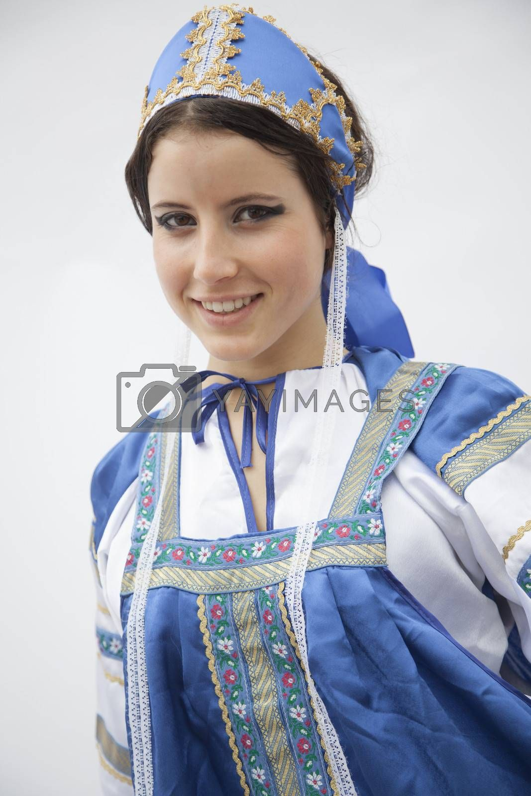 Portrait of young smiling woman in traditional clothing from Russia, studio shot