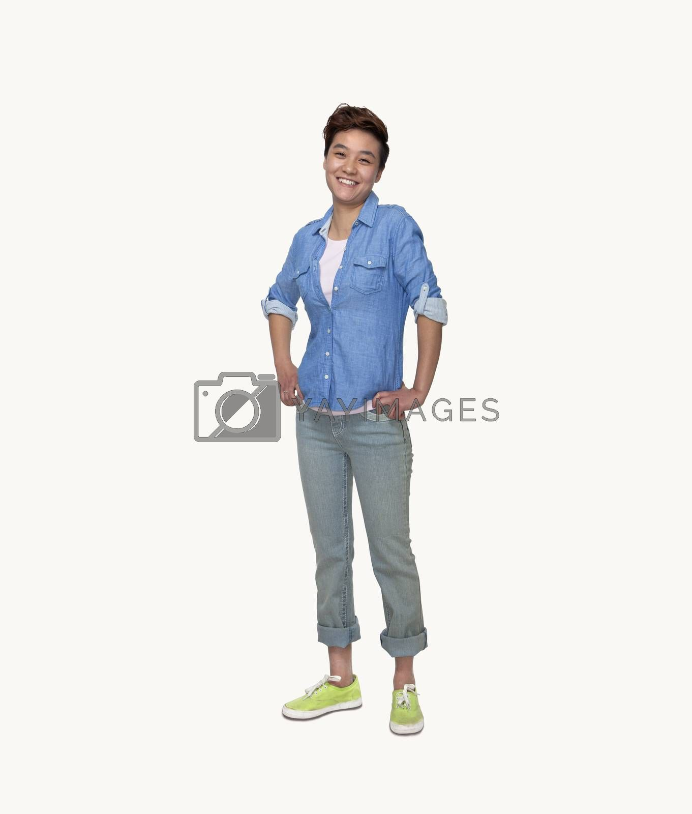 Portrait of smiling young woman in casual clothing, hands on hips, full length, studio shot