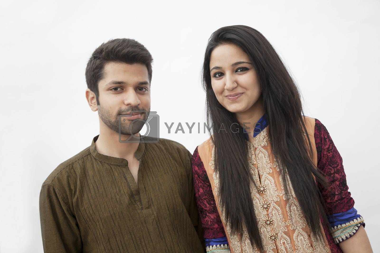 Portrait of smiling young couple wearing traditional clothing from Pakistan, studio shot
