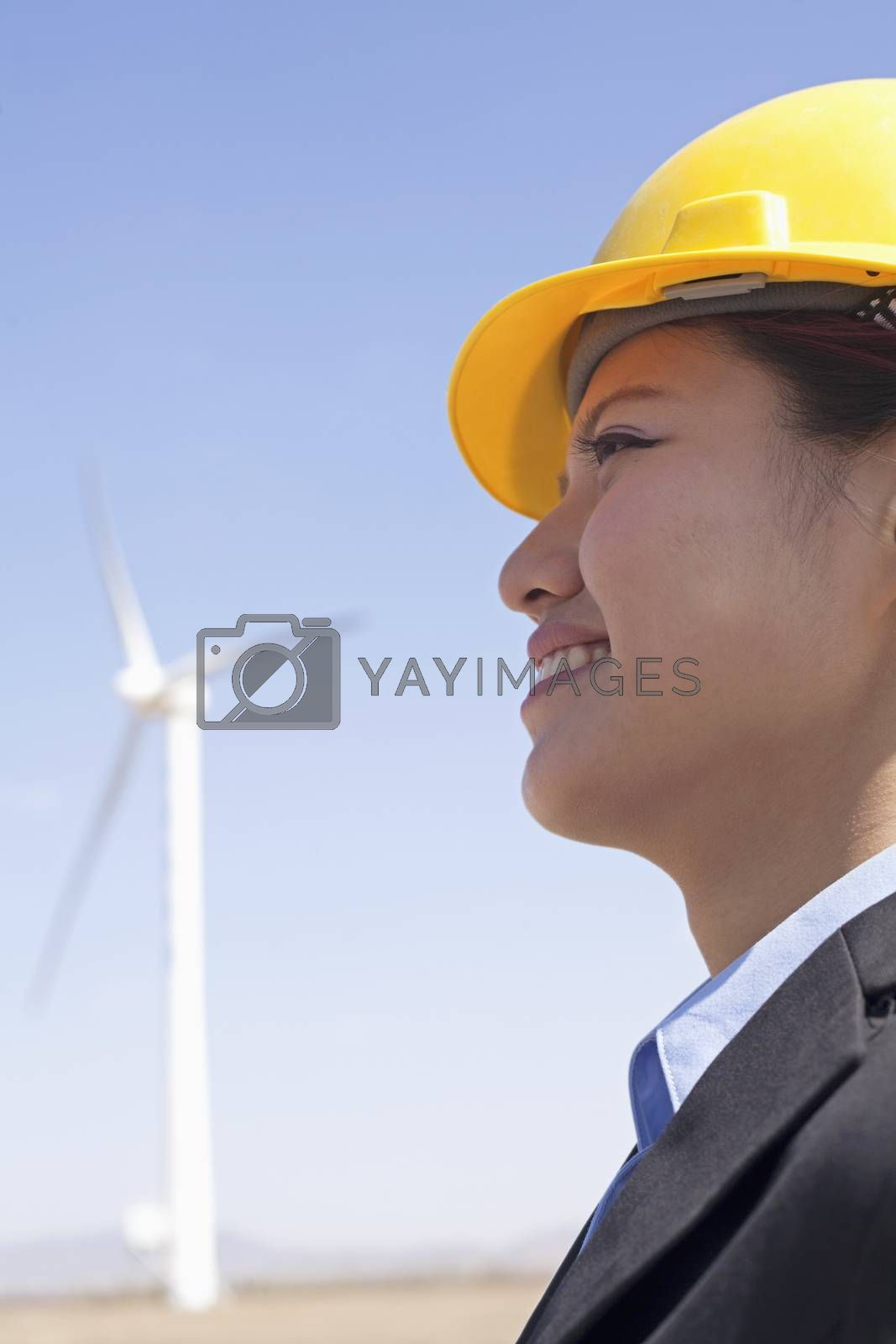 Portrait of young smiling female engineer checking wind turbines on site, side view