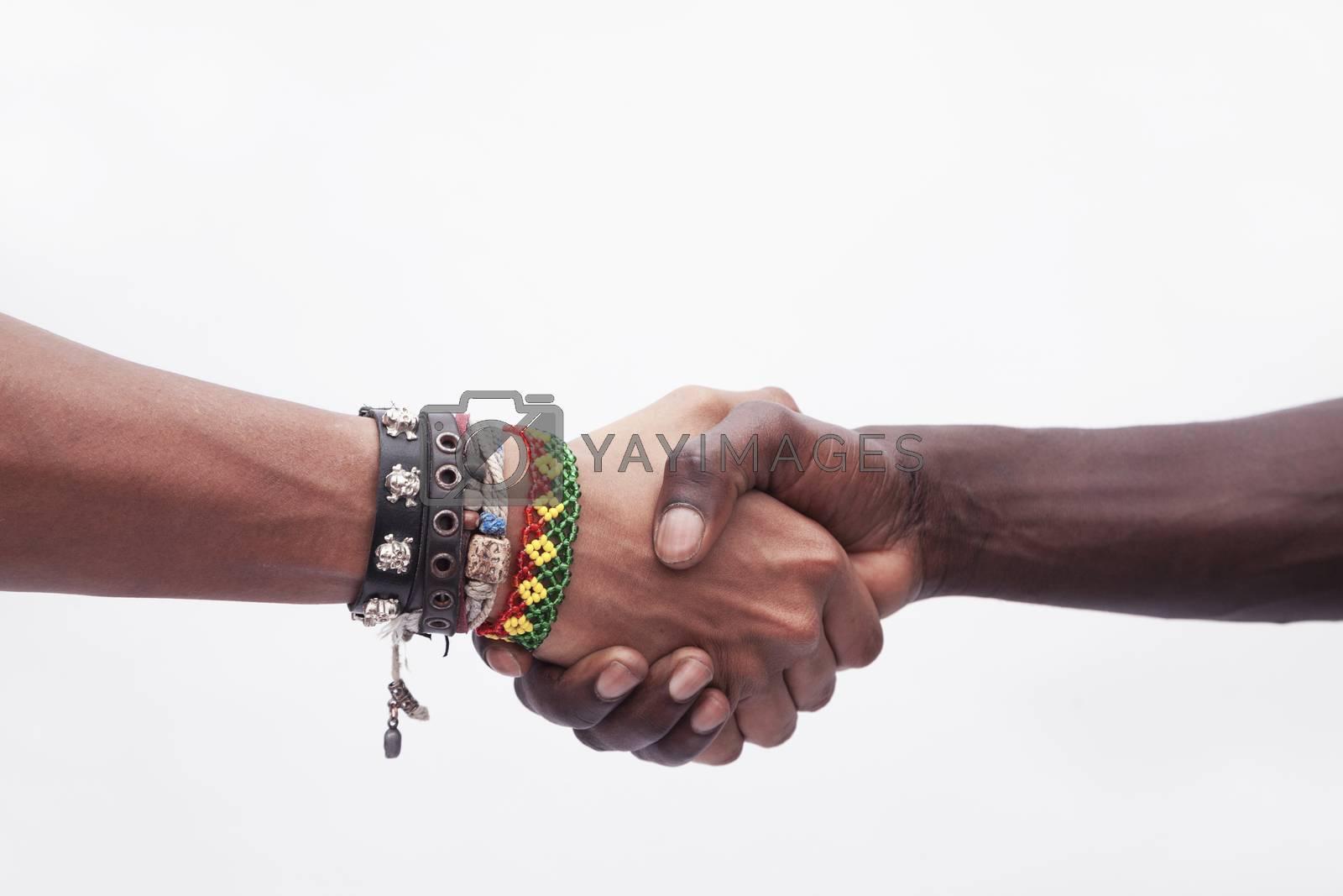 Young woman and man shaking hands, close-up, studio shot
