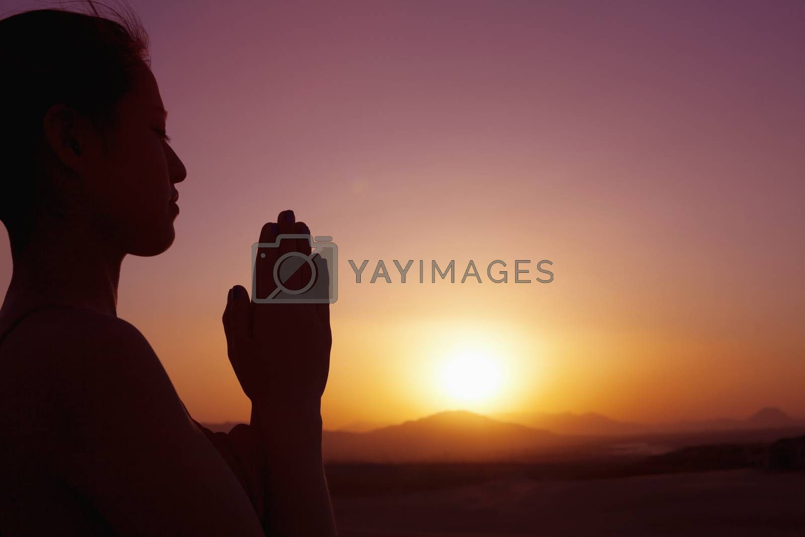Serene young woman with hands together in prayer pose  in the desert in China, silhouette, sun setting, profile