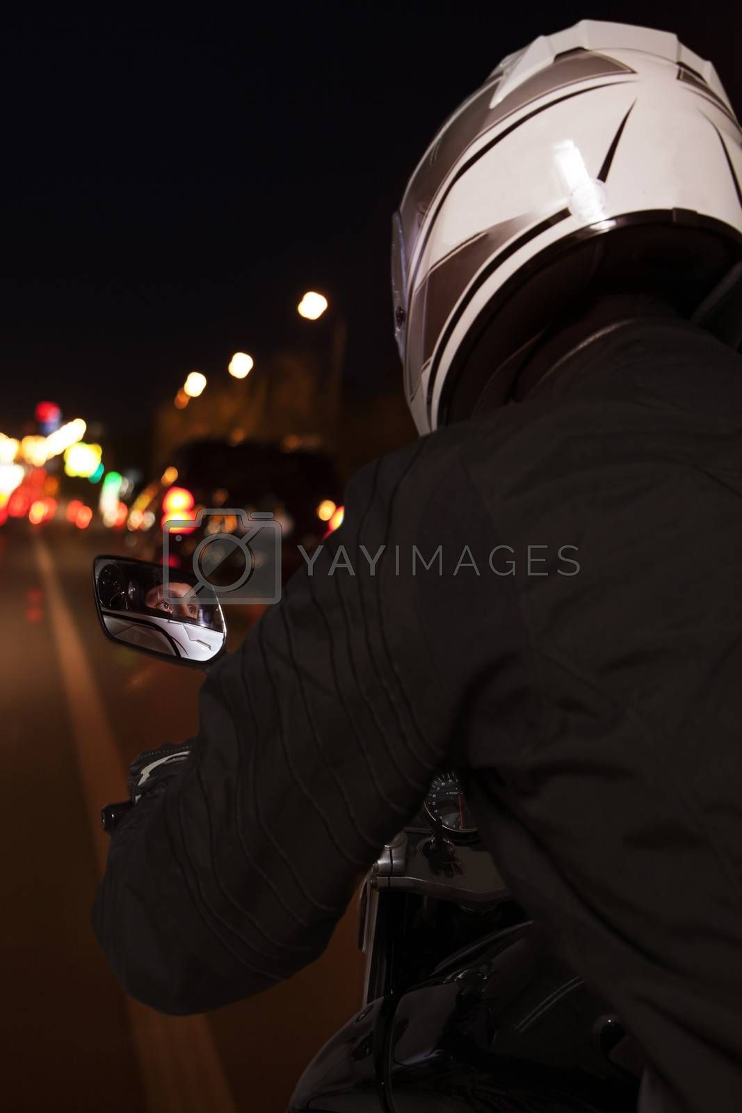 Young man riding a motorcycle through the streets of Beijing at night, rear view