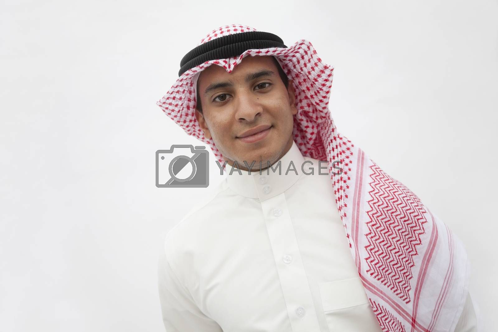 Portrait of smiling teenage boy in traditional Arab clothing, studio shot
