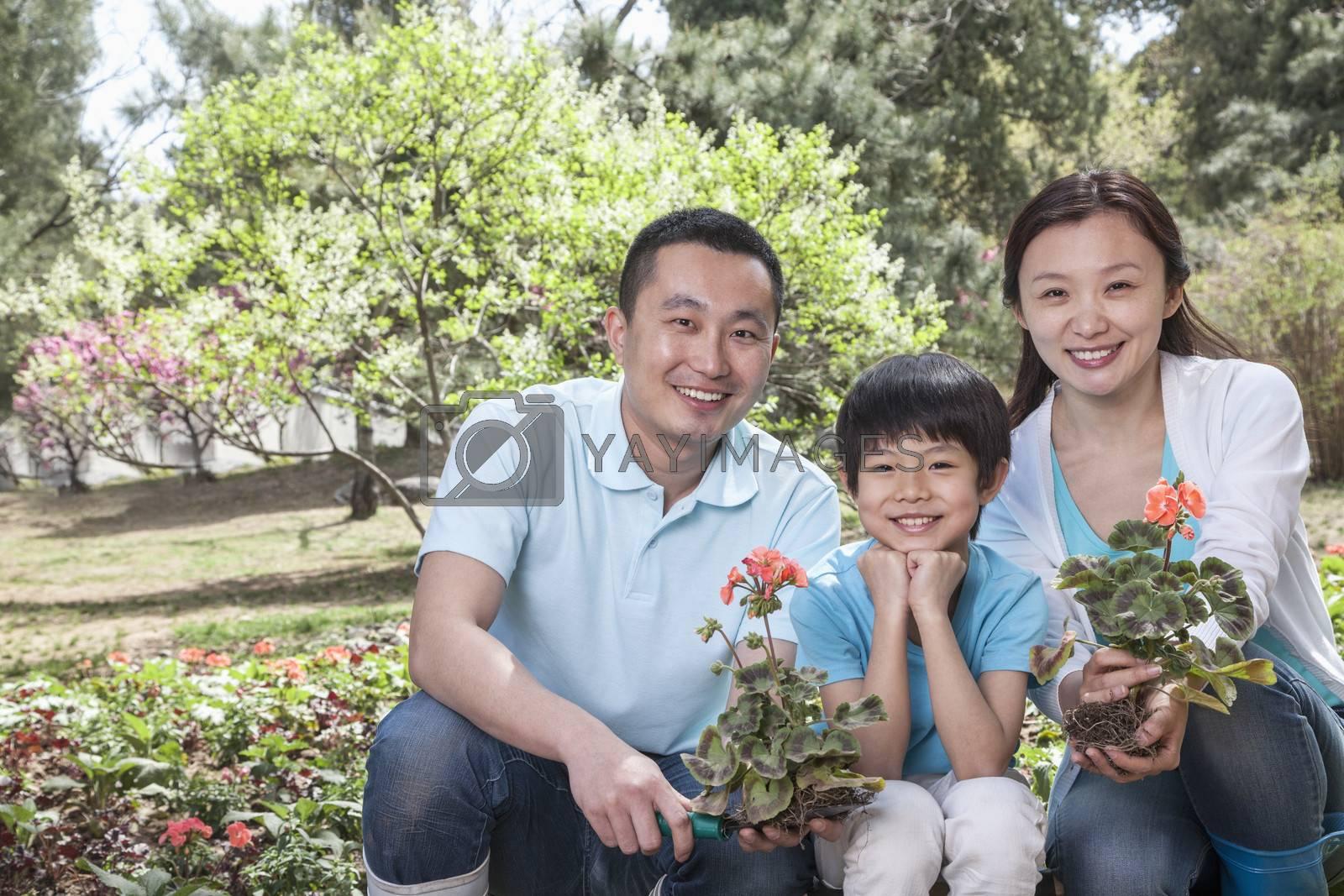 Portrait of family planting flowers.