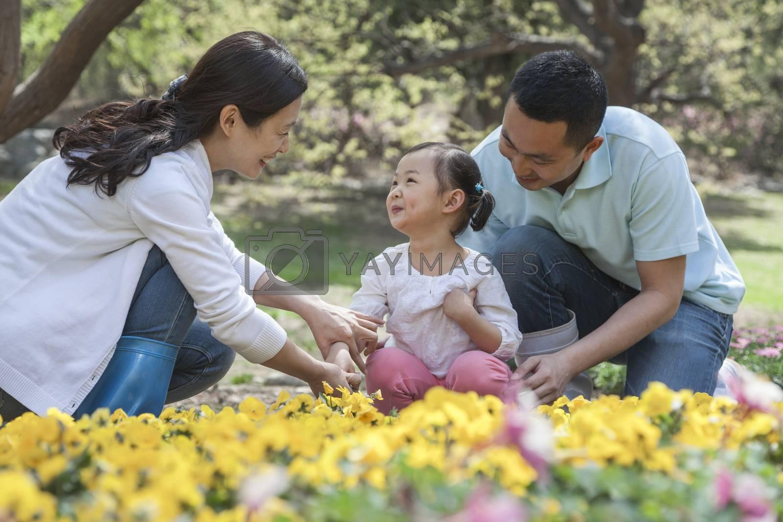 Family sitting in flower garden.