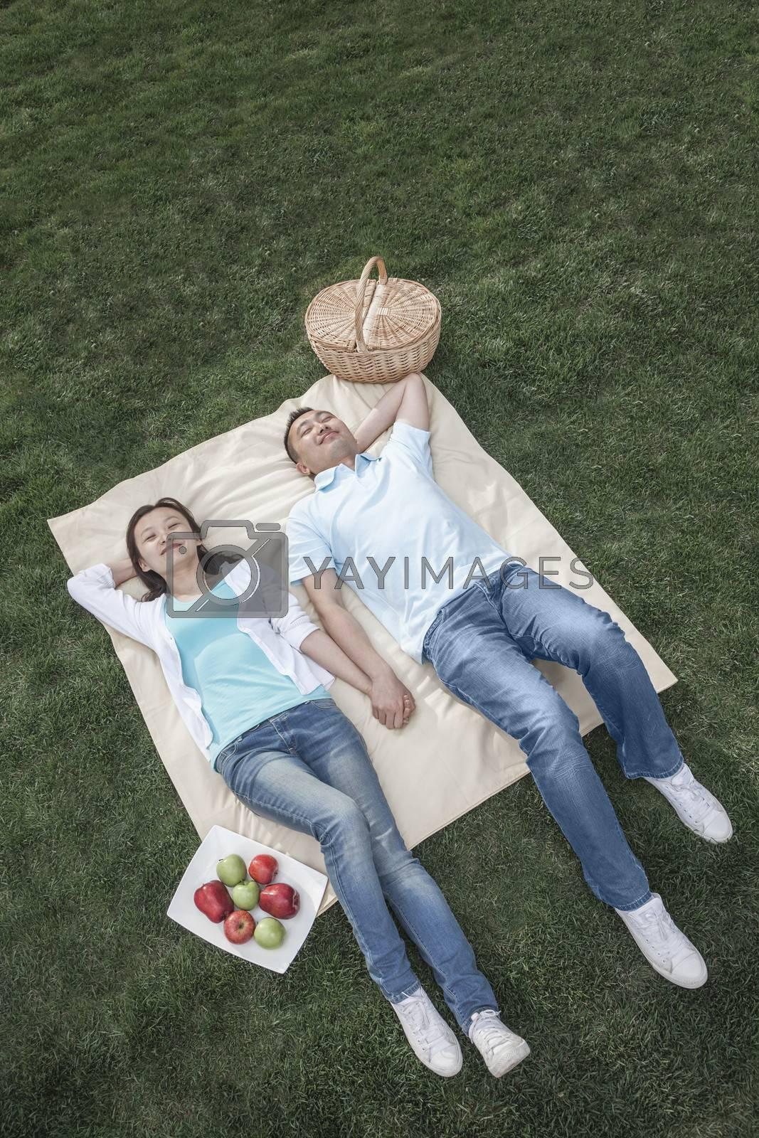 Couple lying on picnic blanket.