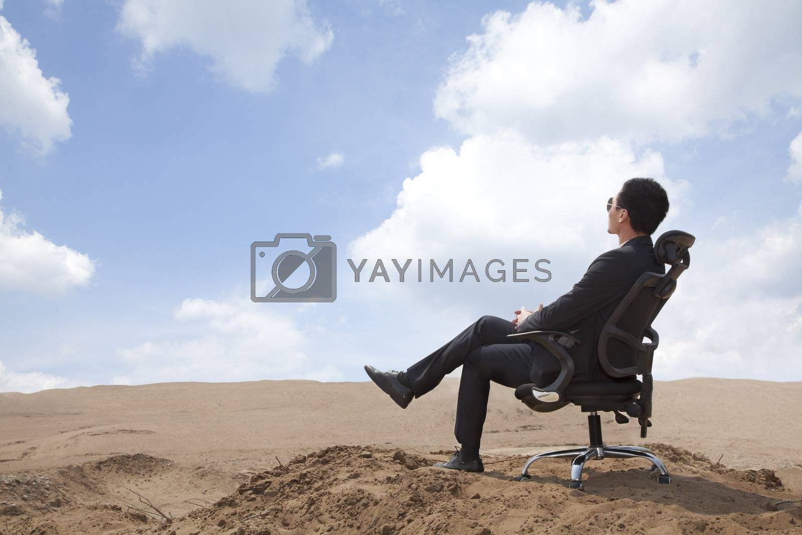 Young businessman sitting in an office chair in the middle of the desert
