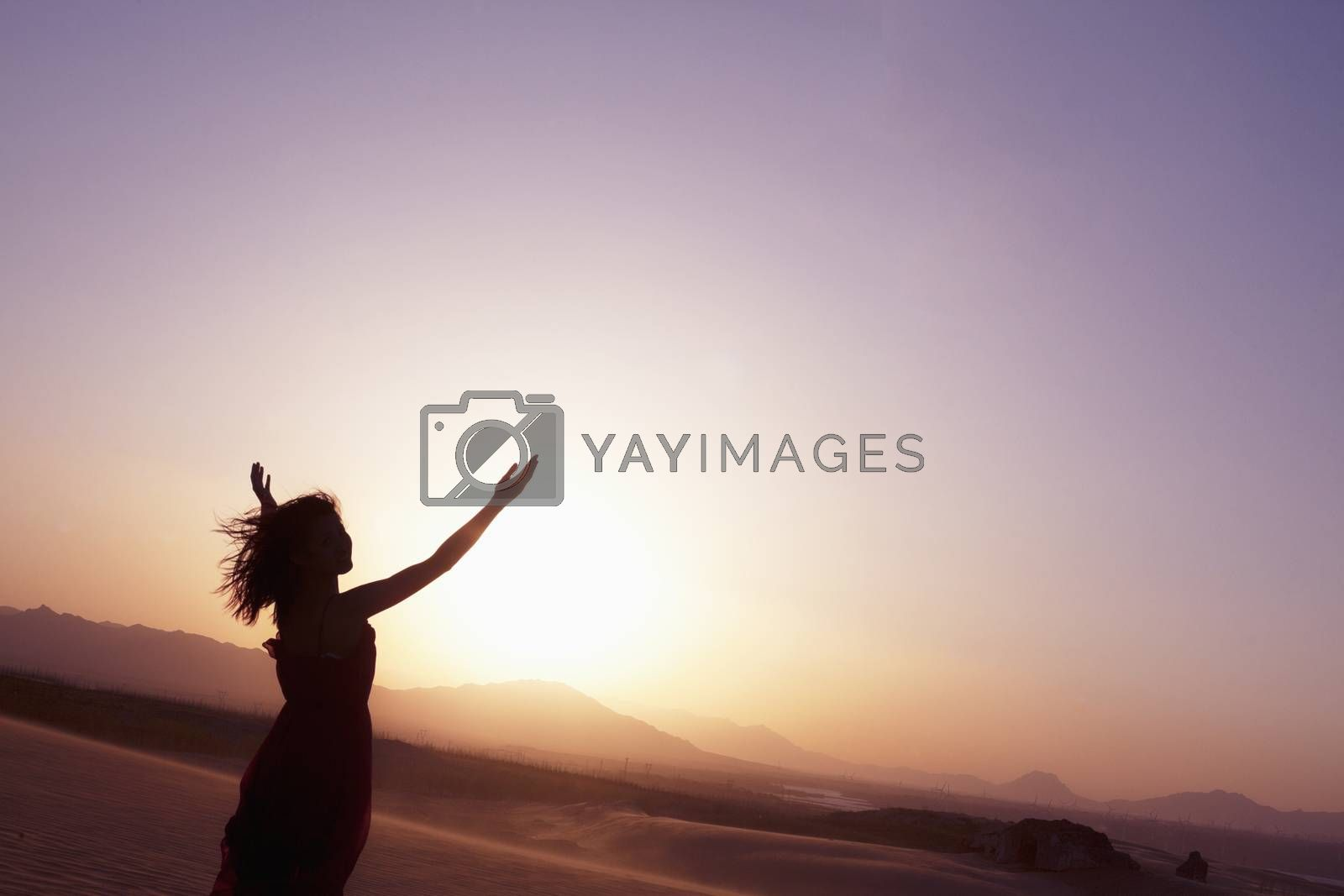 Serene young woman with arms outstretched doing yoga in the desert in China, Silhouette