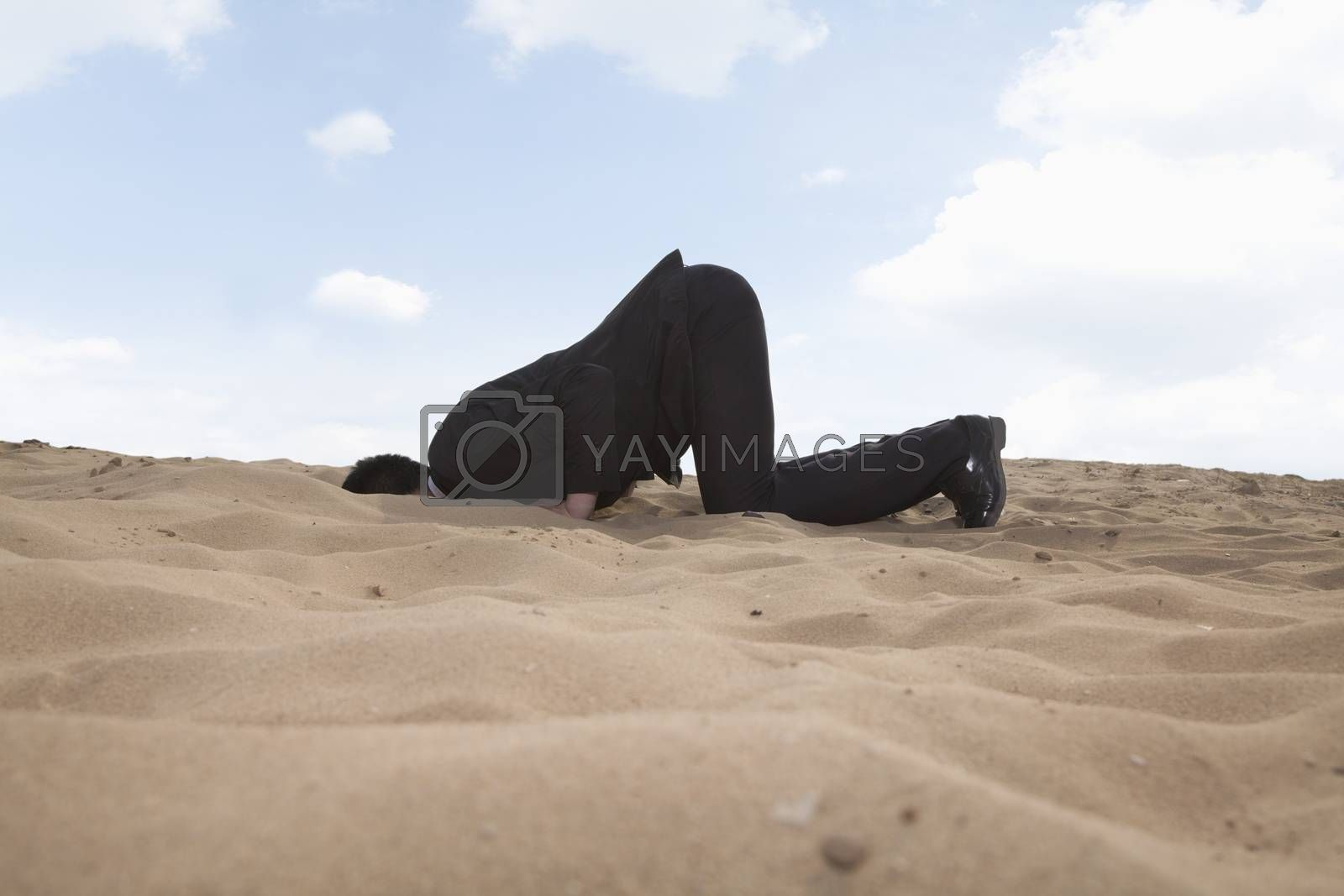 Young businessman kneeling with his head in a hole in the sand by XiXinXing
