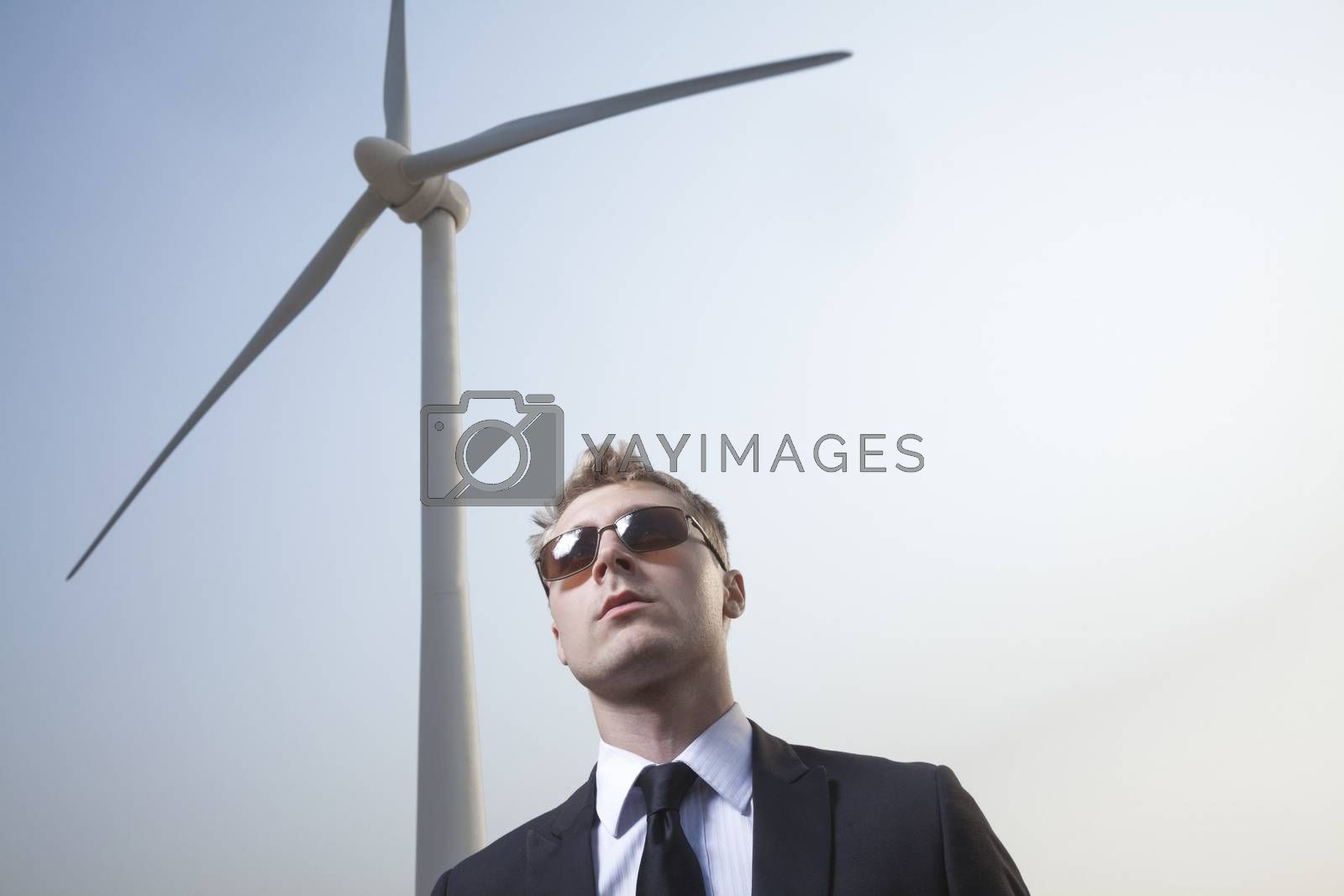 Portrait of serious young businessman in sunglasses standing by a wind turbine by XiXinXing
