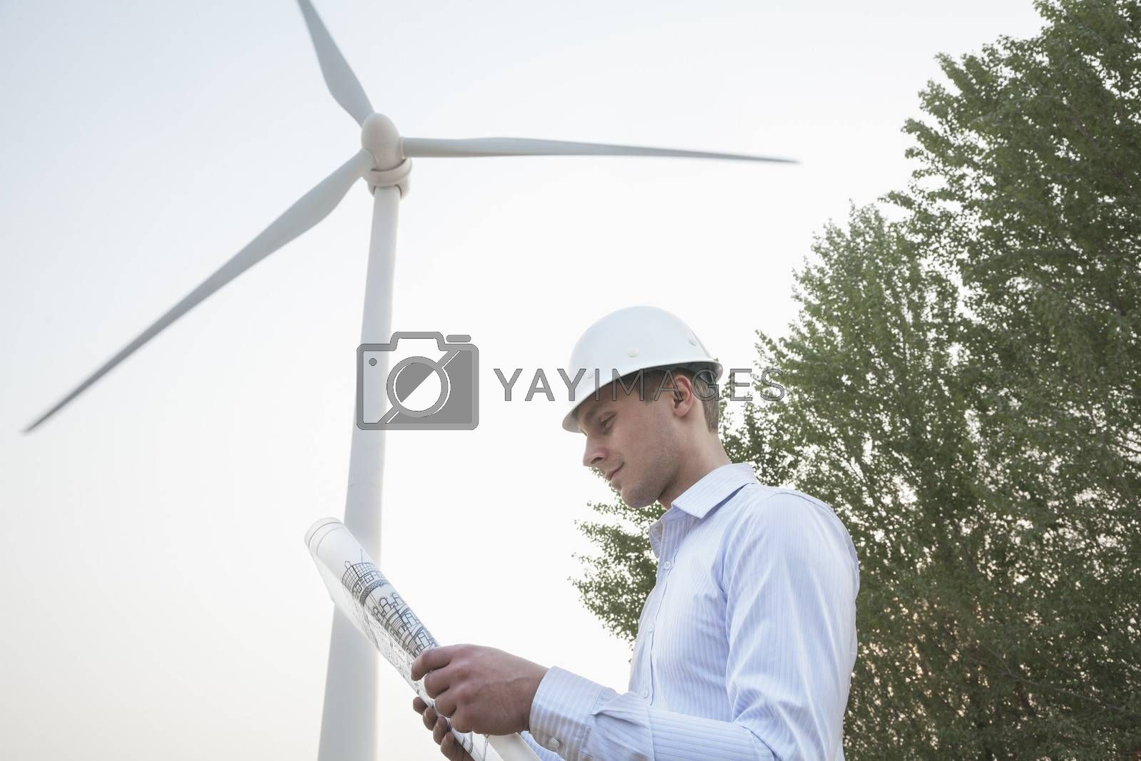 Young male engineer in a hardhat looking down at a blueprint in front of a wind turbine by XiXinXing