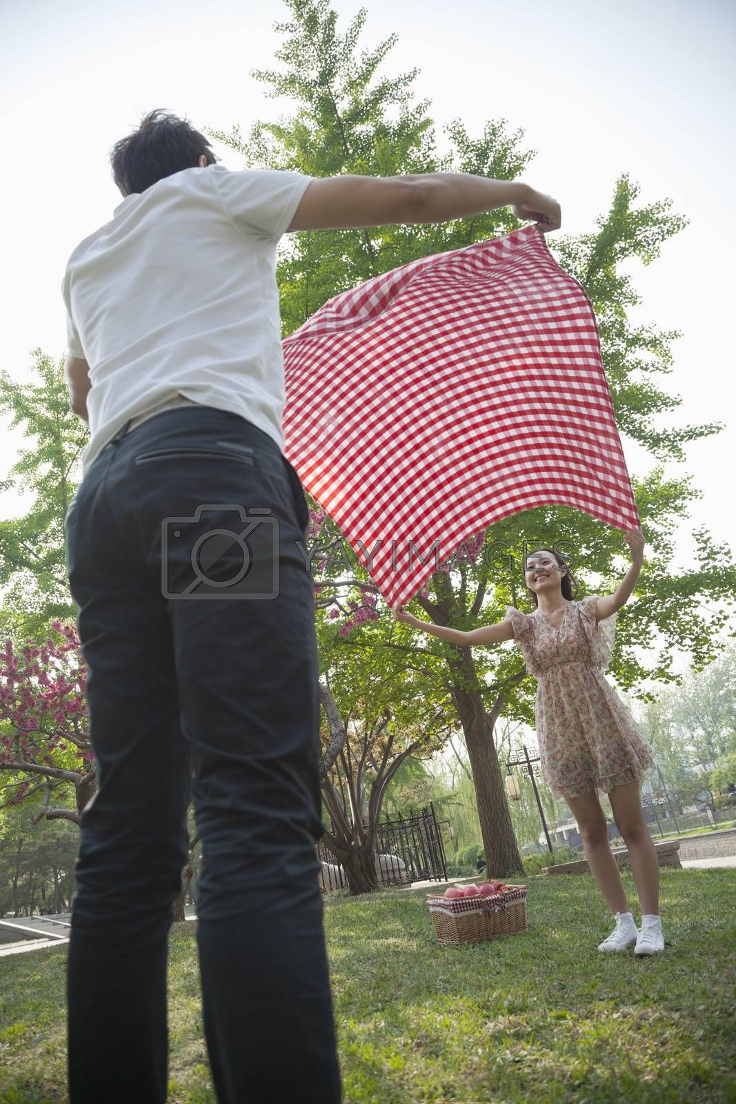 Two friends opening up a checkered blanket and getting ready to have a picnic in the park by XiXinXing