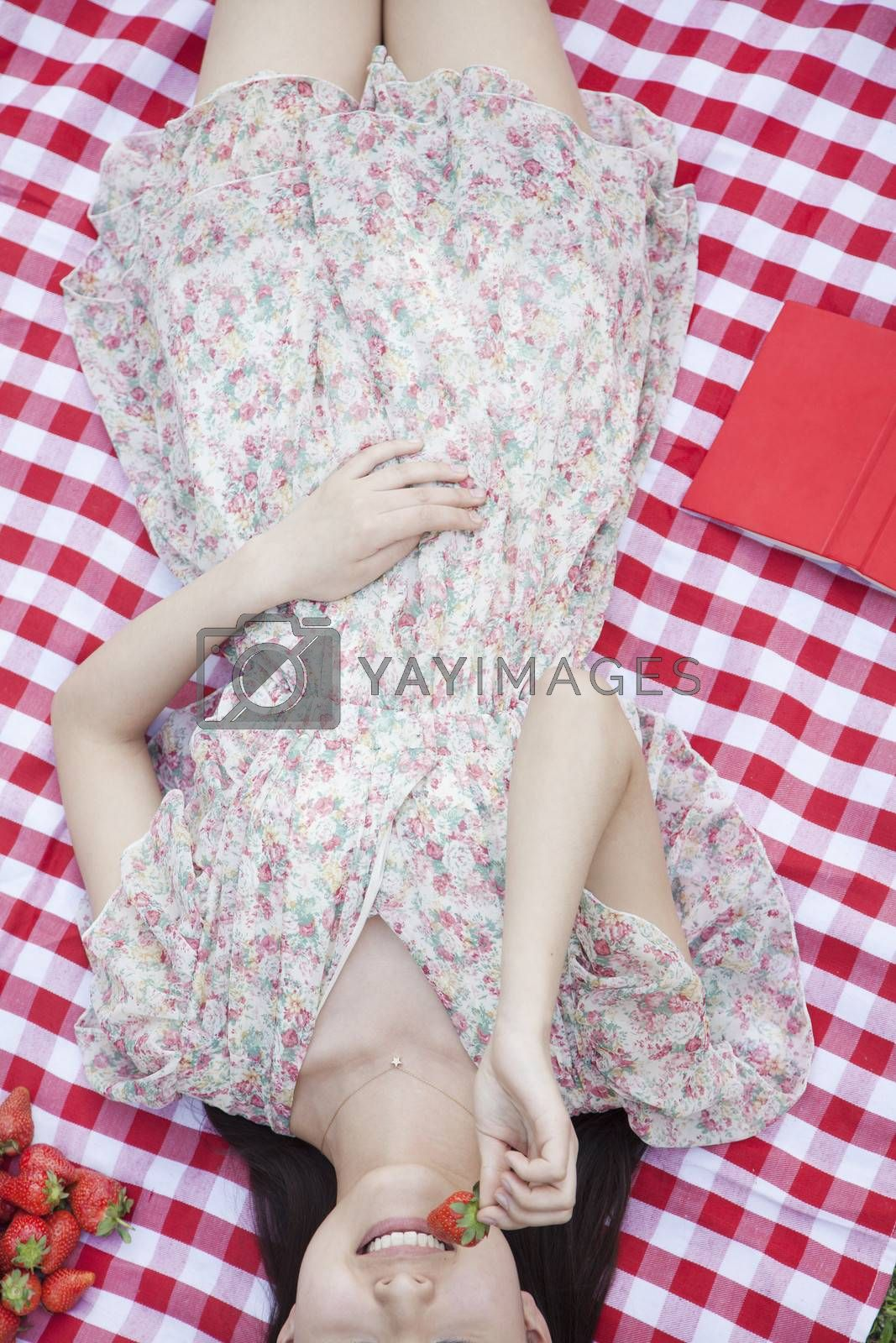 Midsection of a young woman lying on her back on a checkered blanket eating strawberries by XiXinXing