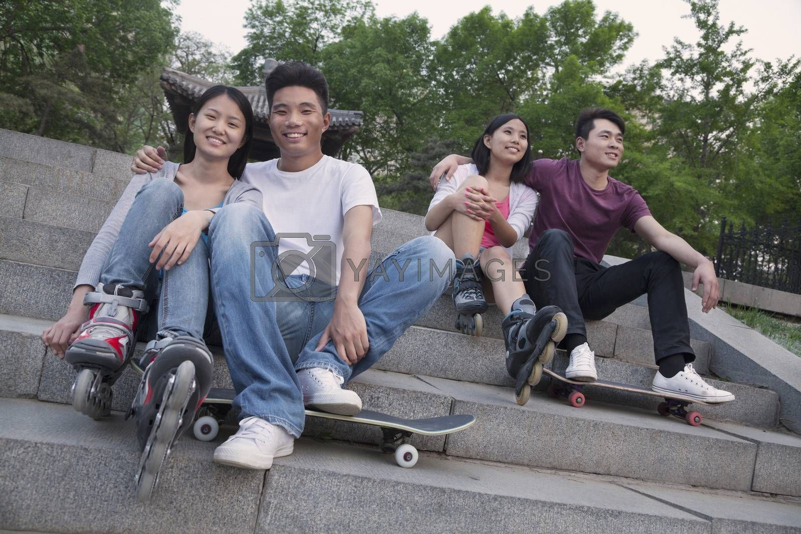 Two young couples sitting and resting on concrete steps outside with skateboards and roller blades by XiXinXing