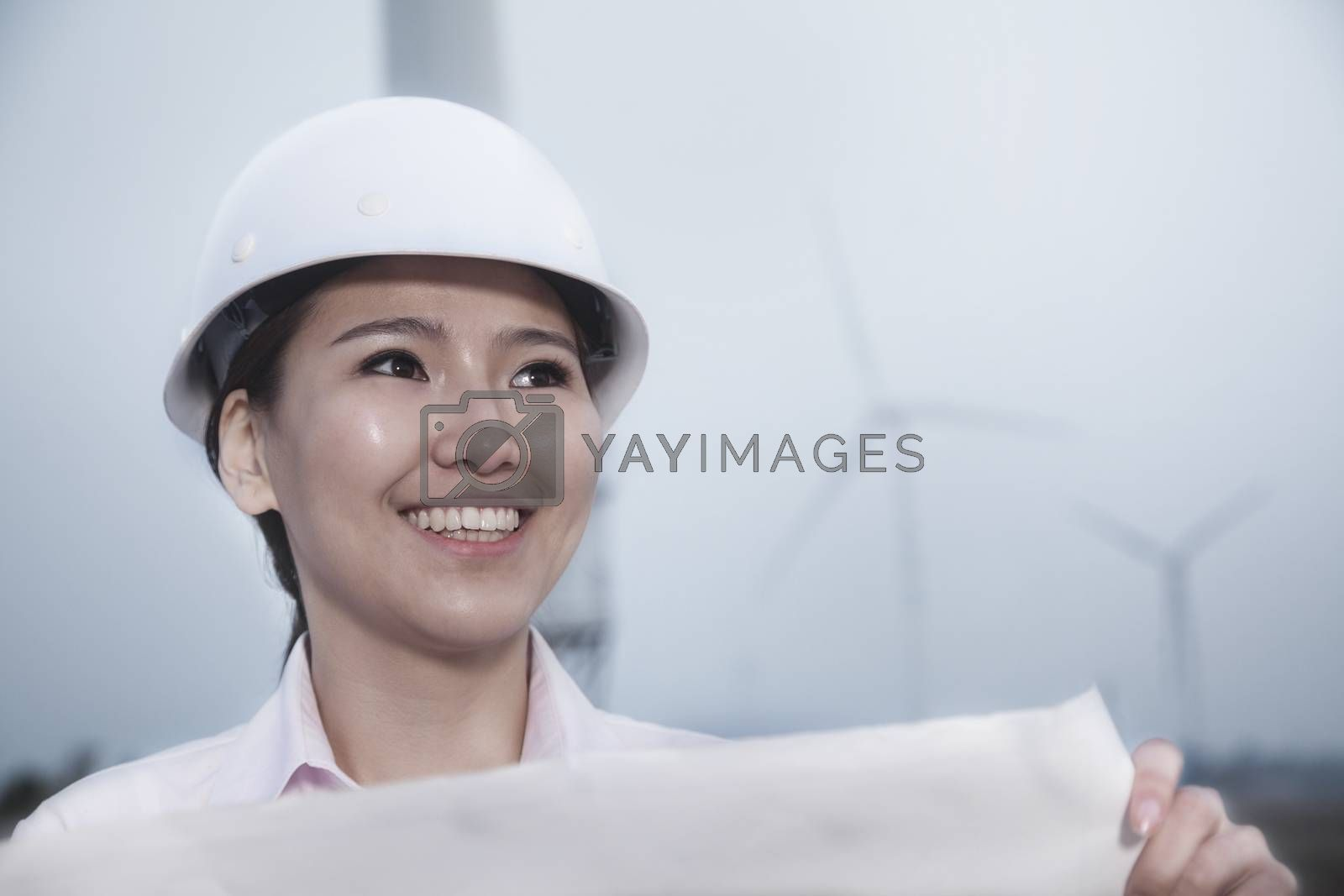 Young smiling female engineer holding a blueprint with wind turbines in the background by XiXinXing