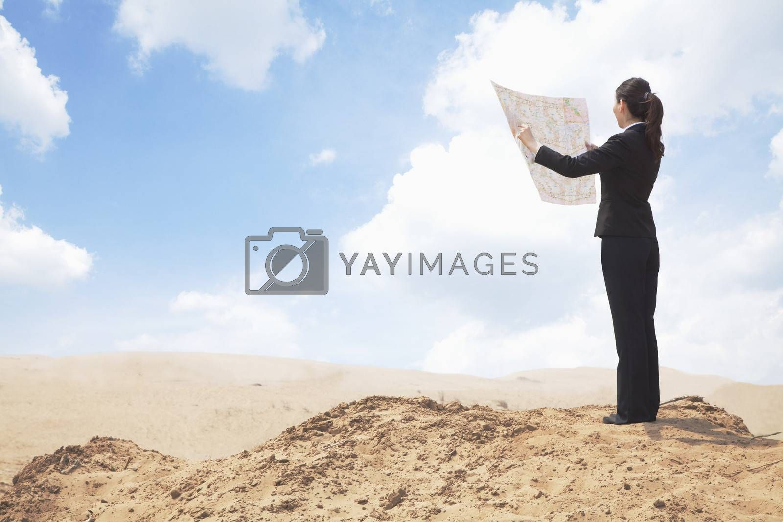 Young Businesswoman looking at a map in the middle of the desert  by XiXinXing