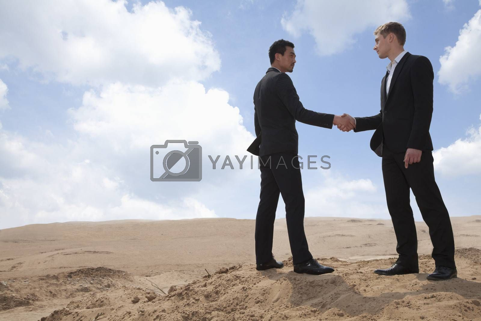 Two young businessmen shaking hands in the middle of the desert, full length by XiXinXing