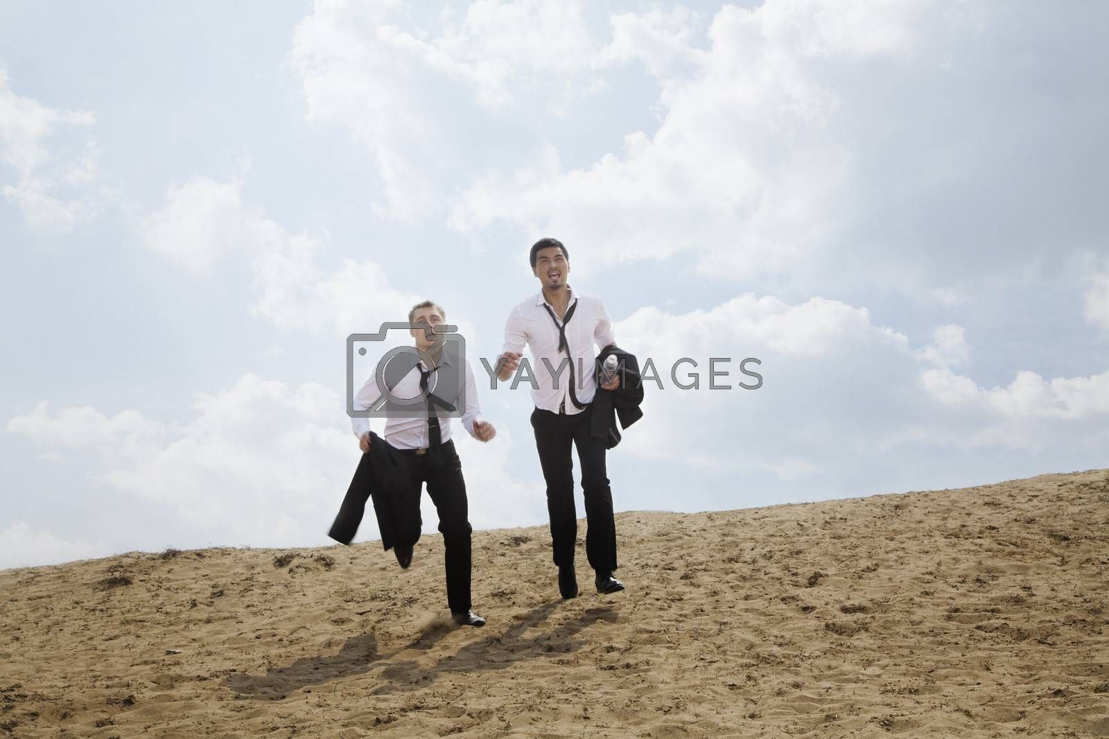 Two young businessmen running and exhausted in the desert, holding jackets by XiXinXing