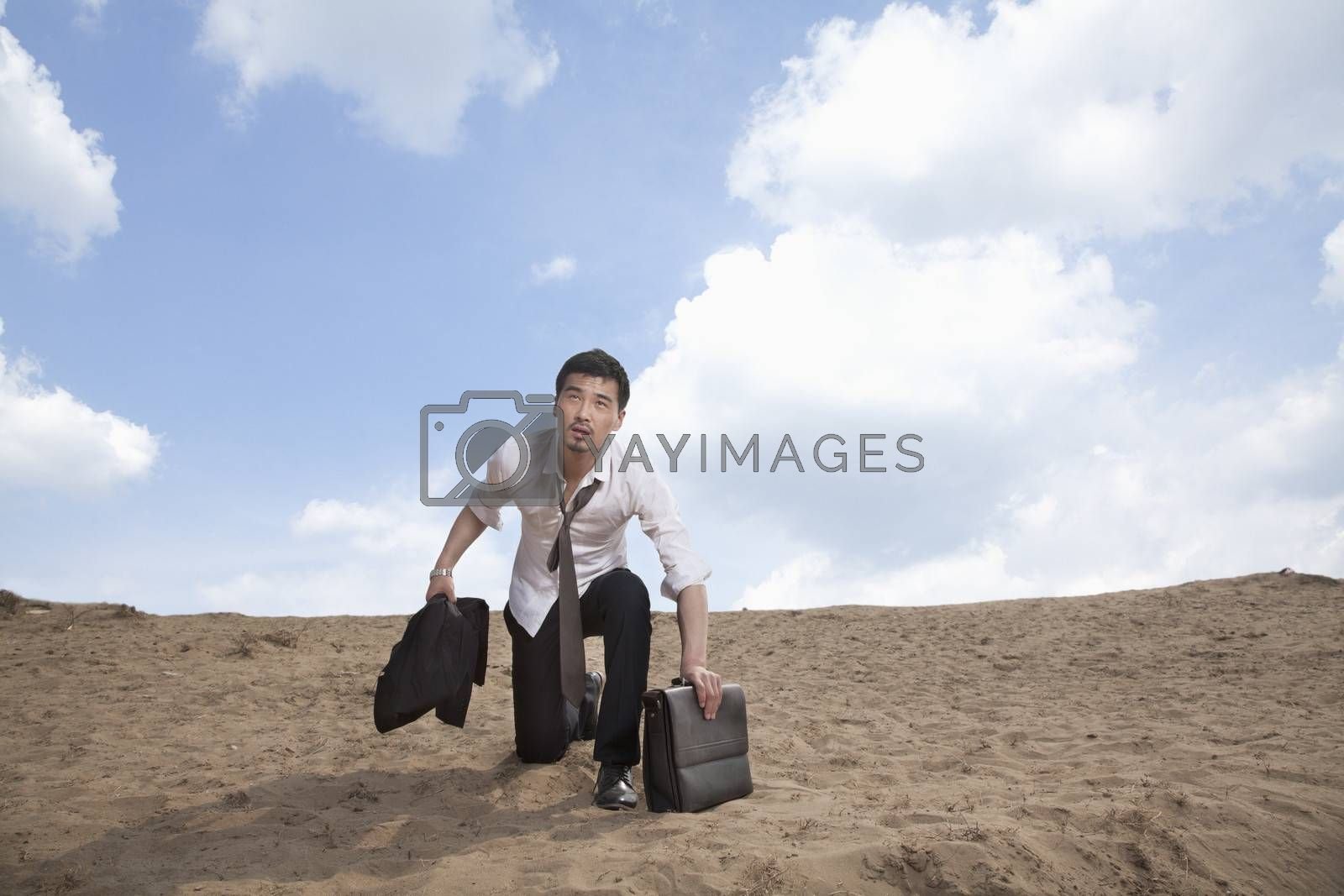 Young businessman kneeling in the desert and holding a briefcase, exhausted by XiXinXing
