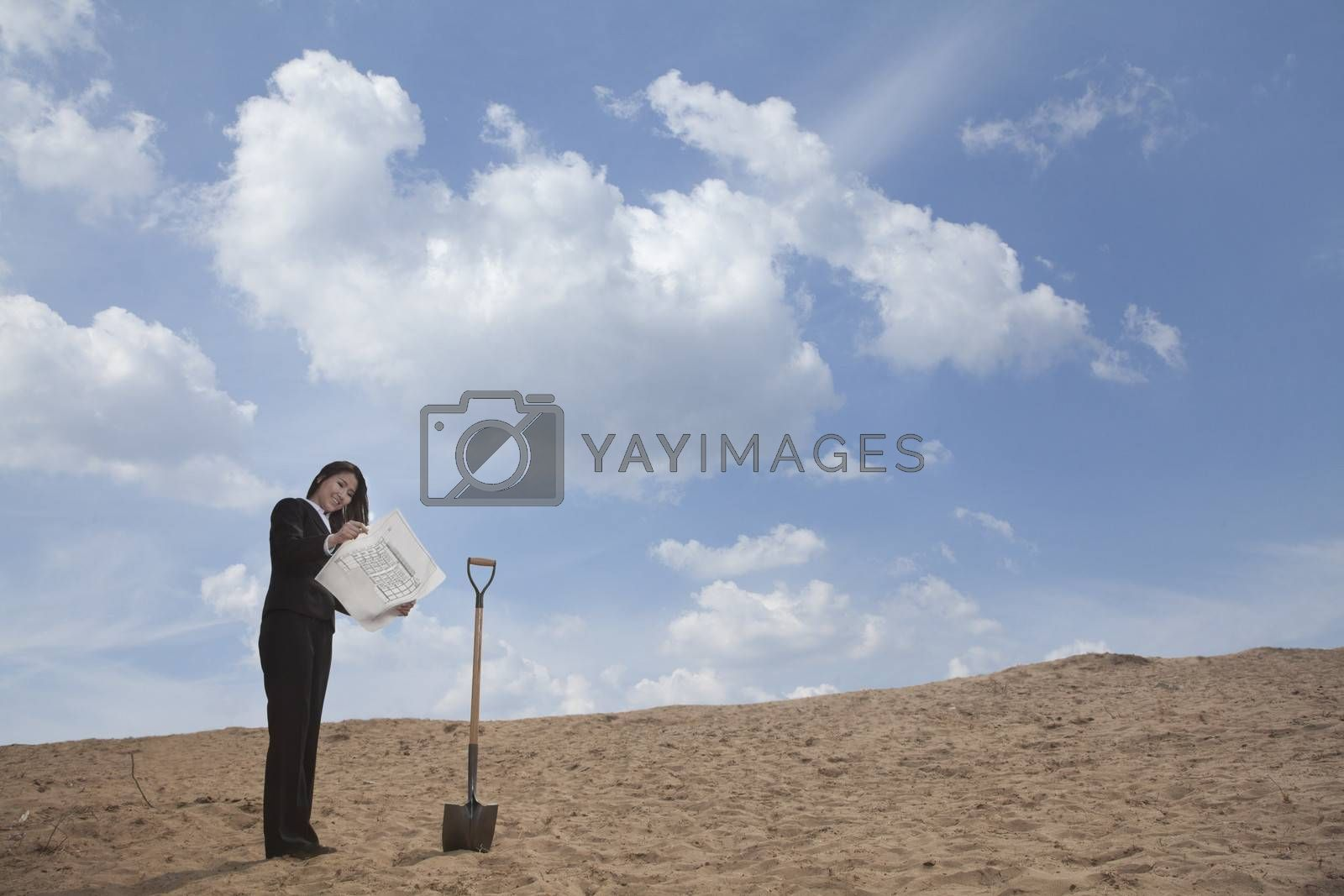 Young businesswoman looking at a blueprint next to a shovel in the middle of the desert by XiXinXing