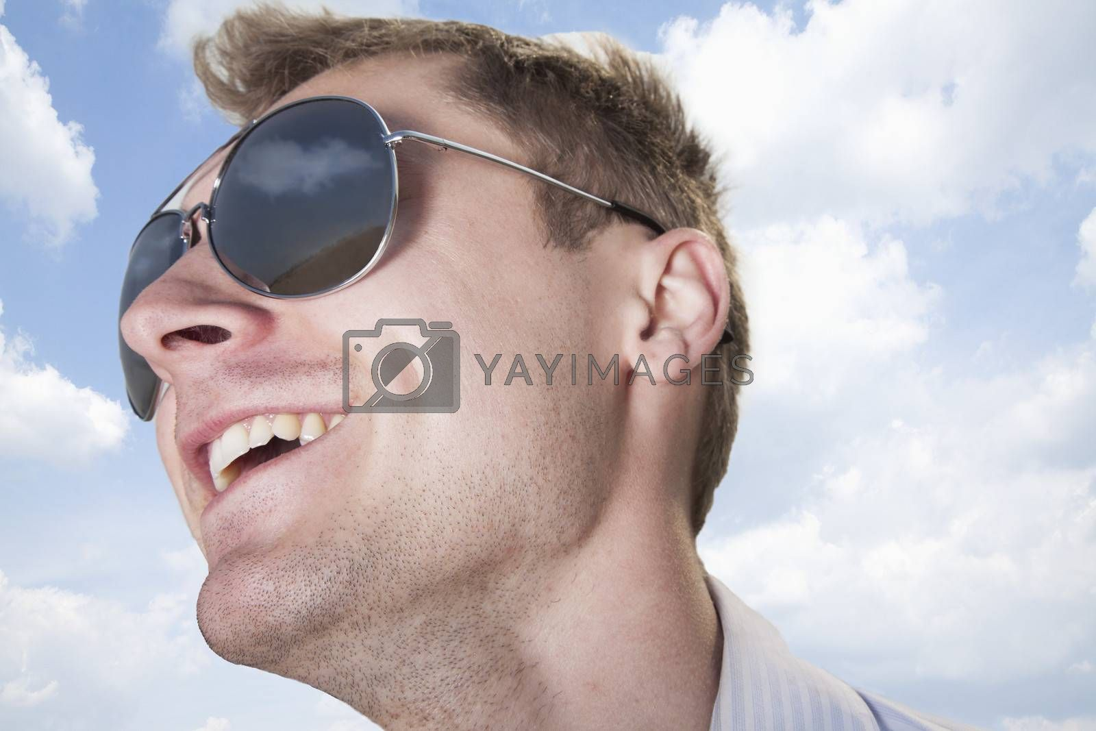 Portrait of young businessman in sunglasses smiling, close-up on face by XiXinXing