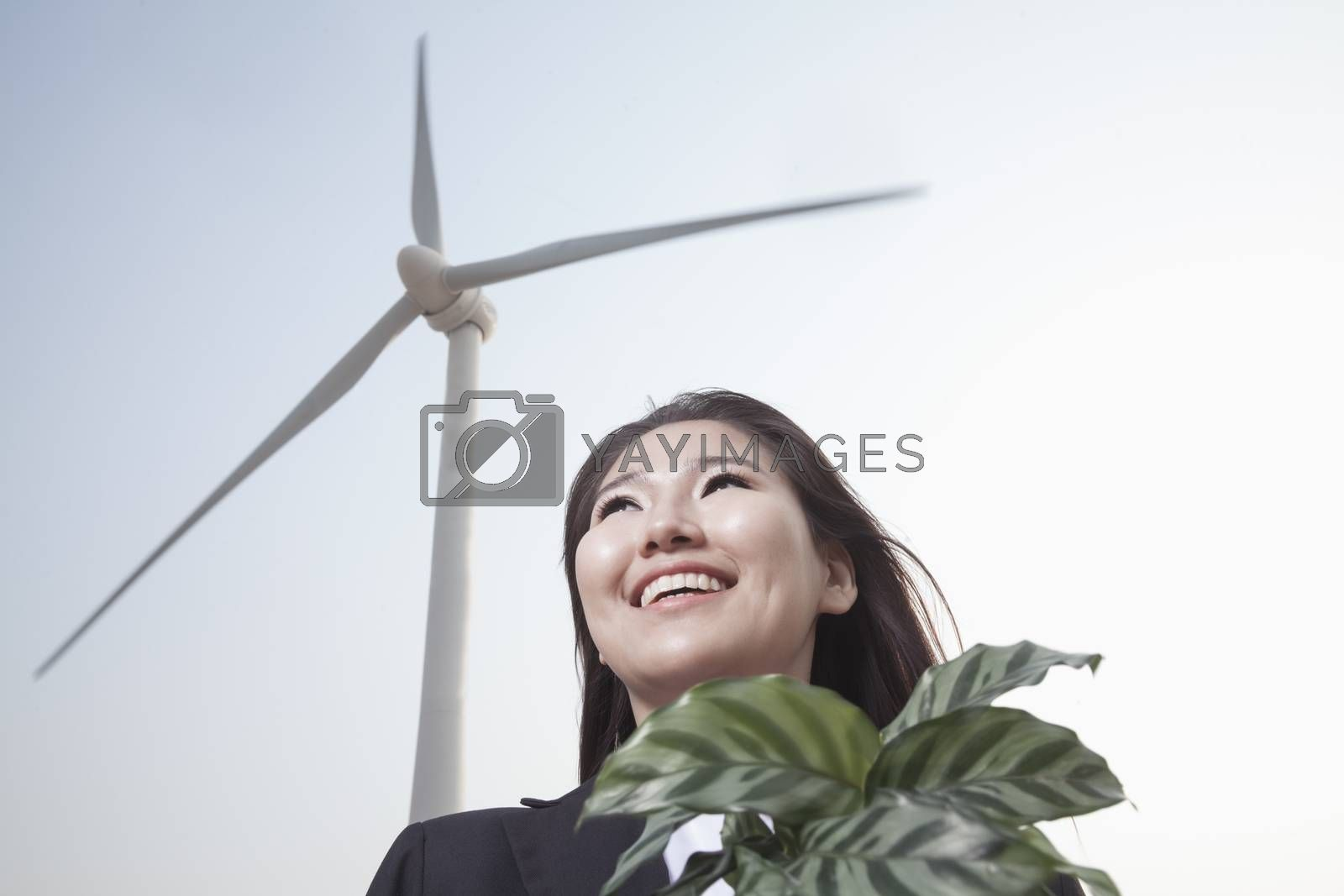 Portrait of smiling young businesswoman standing by a wind turbine and holding a plant by XiXinXing