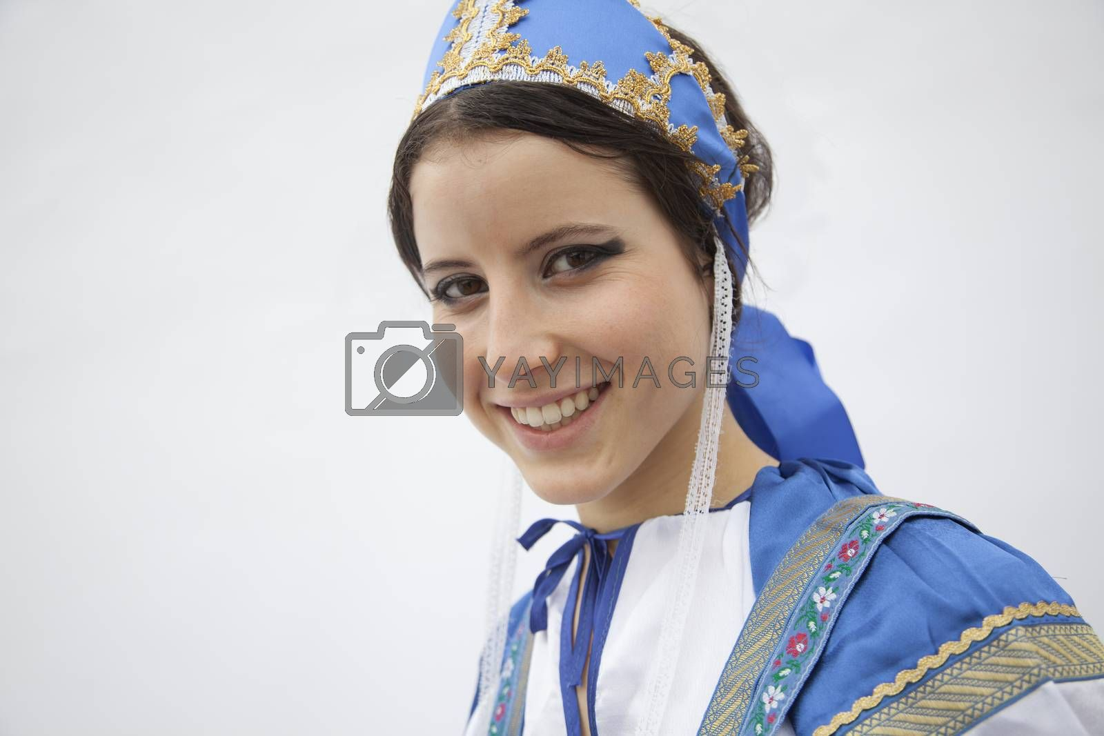 Portrait of young smiling woman in traditional clothing from Russia, studio shot by XiXinXing