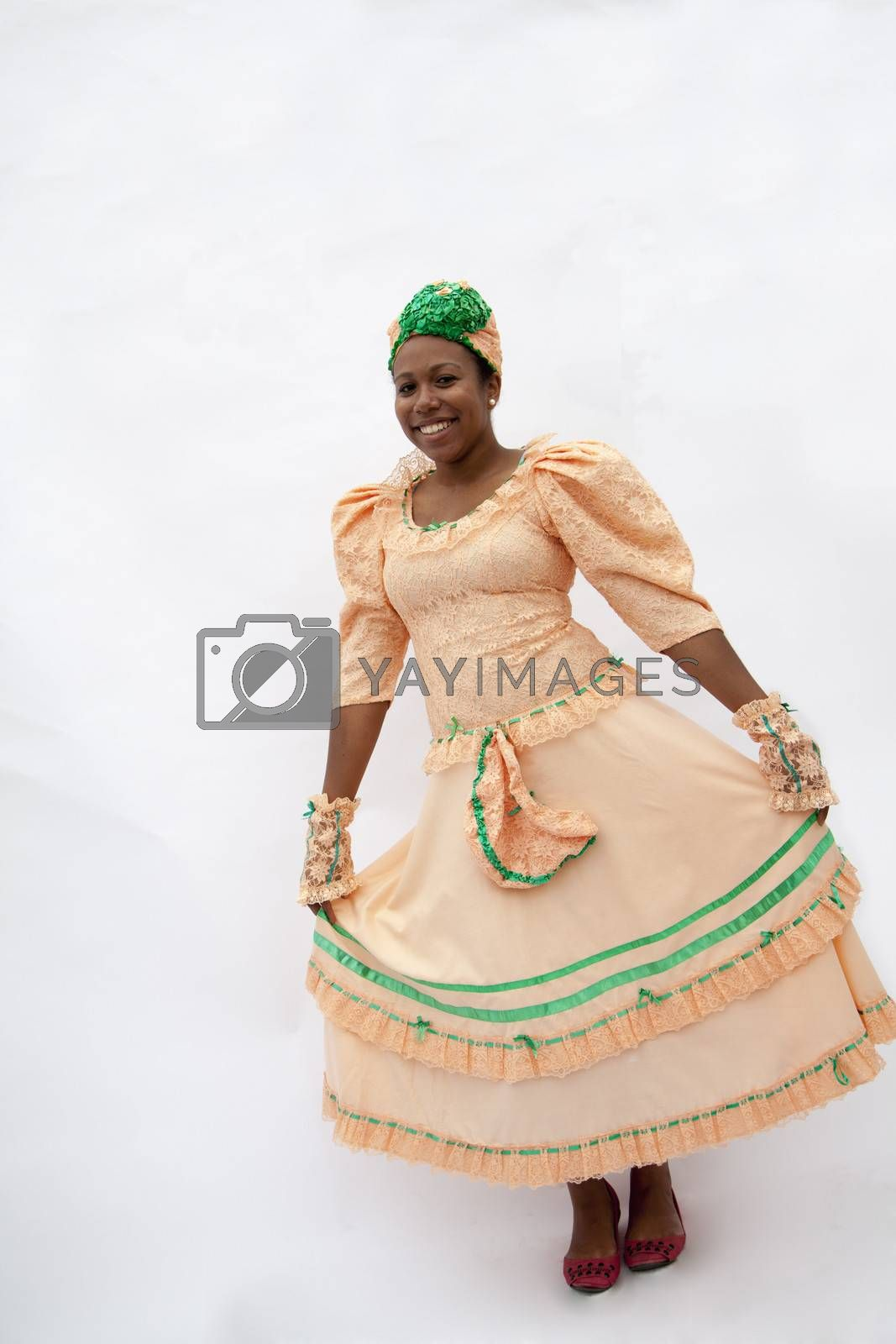 Portrait of young smiling woman holding her skirt in traditional clothing from the Caribbean, studio shot by XiXinXing