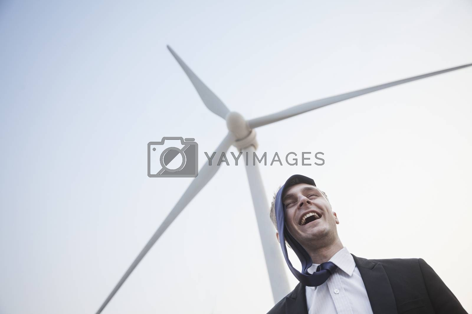 Young smiling businessman standing beside a wind turbine, tie is on his head by XiXinXing